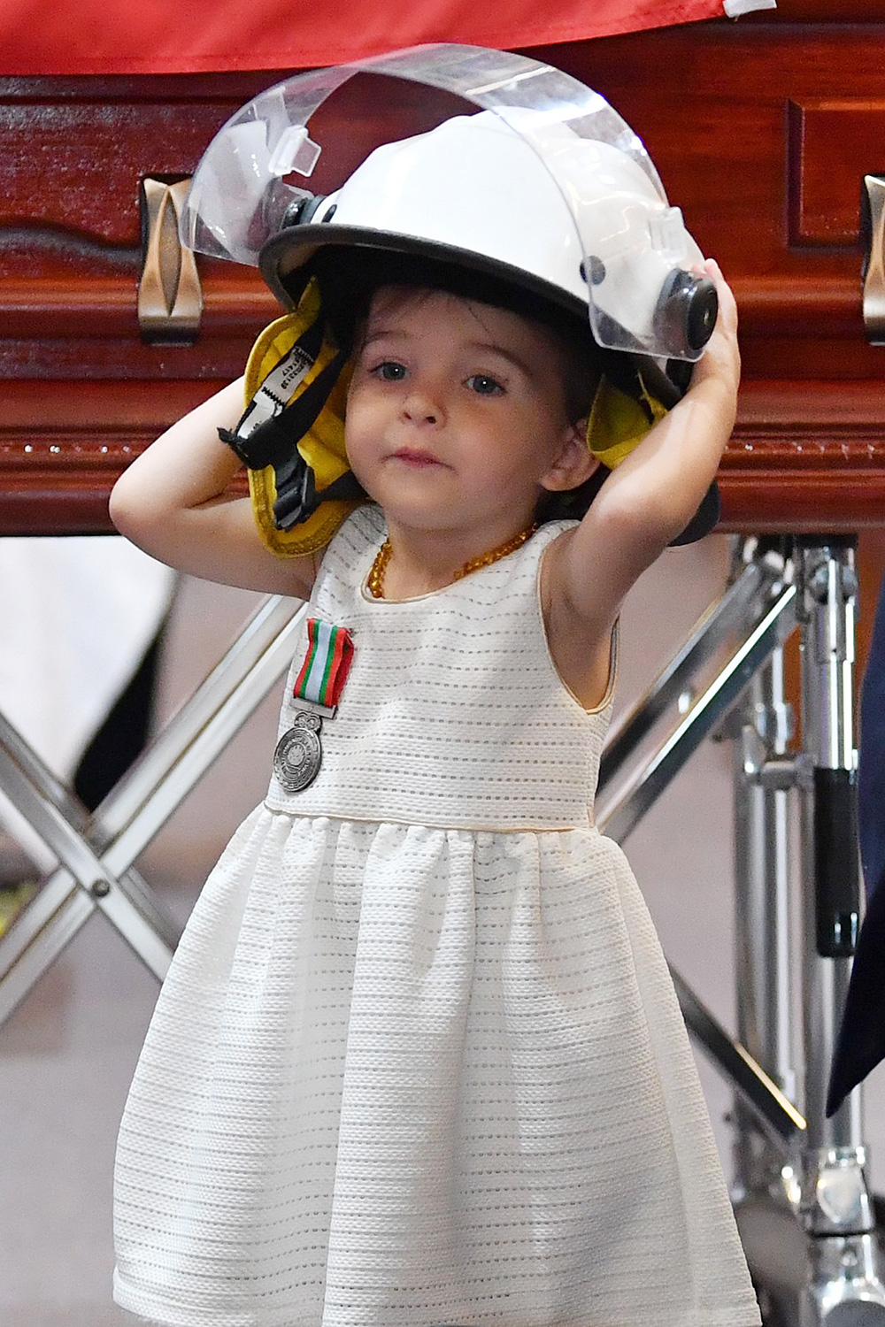 Charlotte O'Dwyer, daughter of late New South Wales (NSW) Rural Fire Service (RFS) volunteer Andrew O'Dwyer, wears her father's helmet during a funeral, at Our Lady of Victories Catholic Church in Horsley Park, Sydney, Australia, 07 January 2020