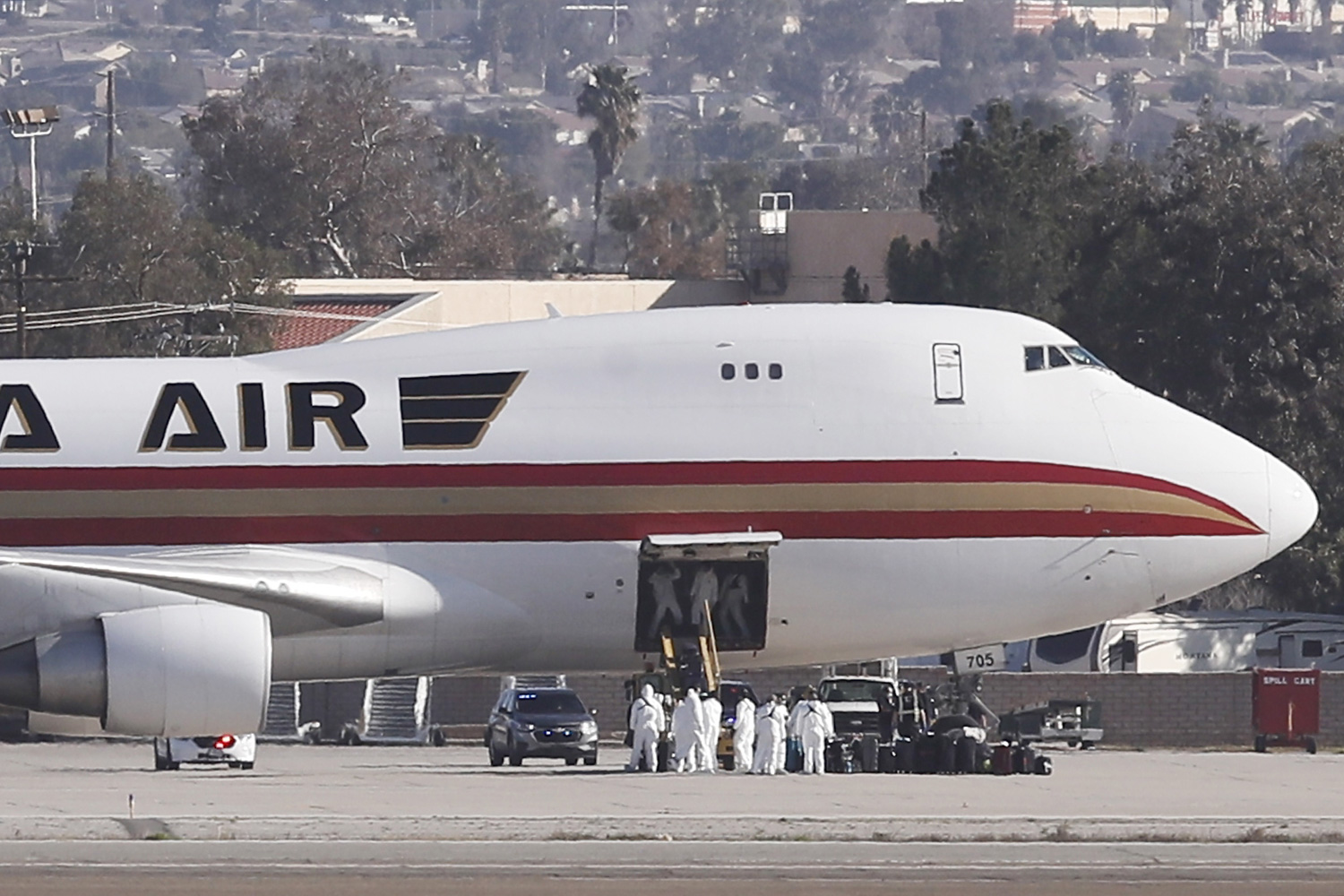 People in hazmat suits are seen outside of the Kalitta Air Boeing 747-400 freighter as buses approach the aircraft at the March Air Reserve Base carrying about 200 American evacuees in Riverside, California, USA, 29 January 2020