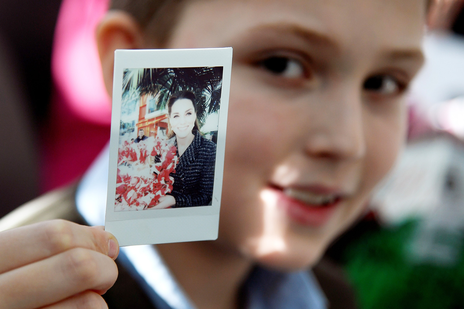Luke Wheeler-Waddison, 10, holds up a polaroid photograph of Britain's Catherine, Duchess of Cambridge which he took during her visit to the Evelina London Childrens Hospital in London on January 28, 2020 to join a creative workshop run by the National Portrait Gallerys Hospital Programme