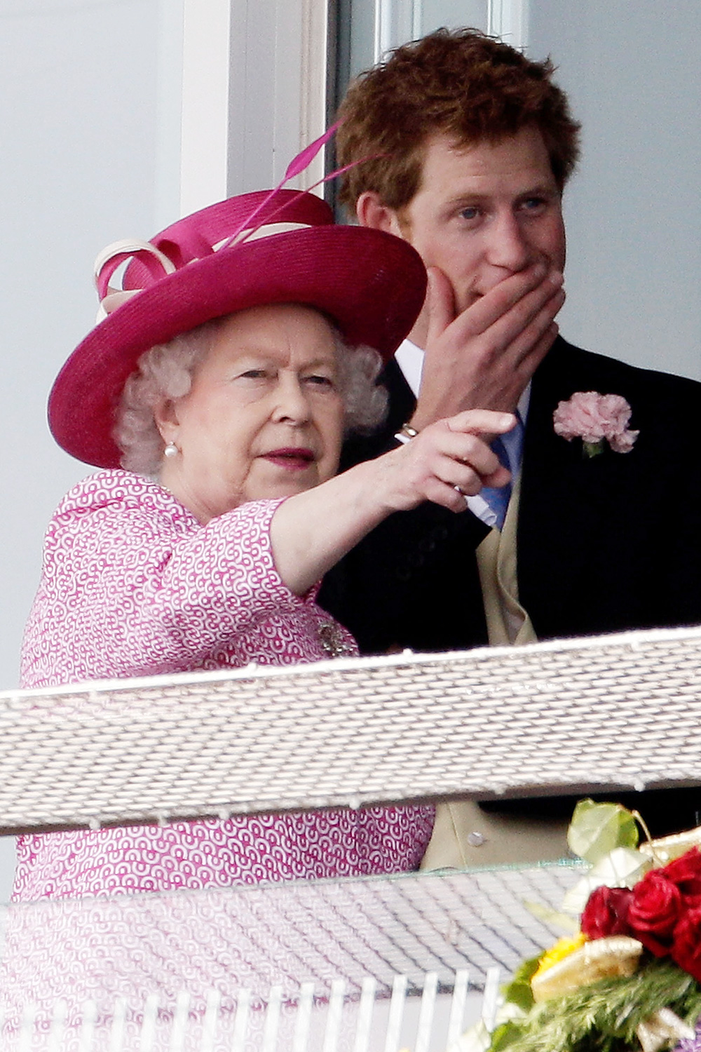 Queen Elizabeth II II and Prince Harry watch a race at Epsom Downs Racecourse on Derby Day on June 4, 2011 in Epsom, England