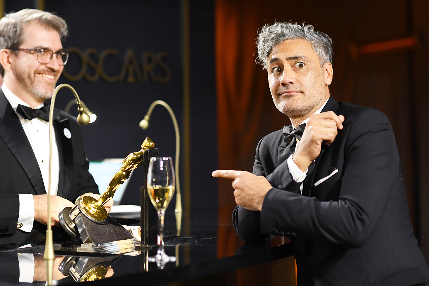 """Taika Waititi (R) waits as his award for Best Adapted Screenplay for """"Jojo Rabbit"""" is engraved as he attends the 92nd Oscars Governors Ball at the Hollywood & Highland Center in Hollywood, California on February 9, 2020"""