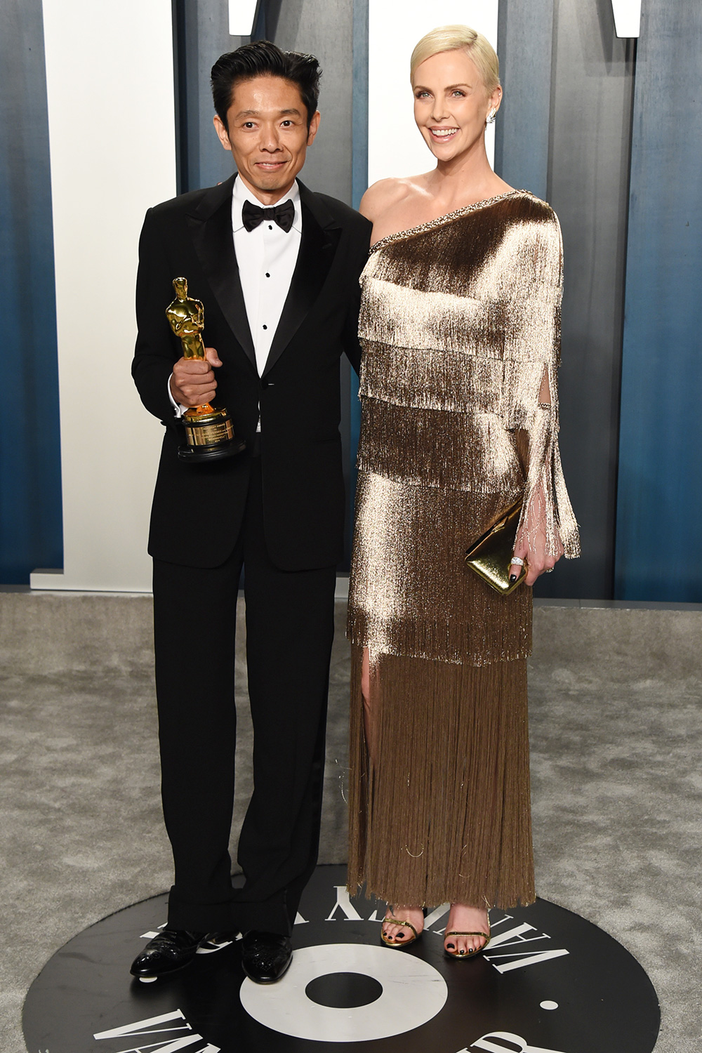 Kazuhiro Tsuji (L) and Charlize Theron attend the 2020 Vanity Fair Oscar Party hosted by Radhika Jones at Wallis Annenberg Center for the Performing Arts on February 09, 2020 in Beverly Hills, California
