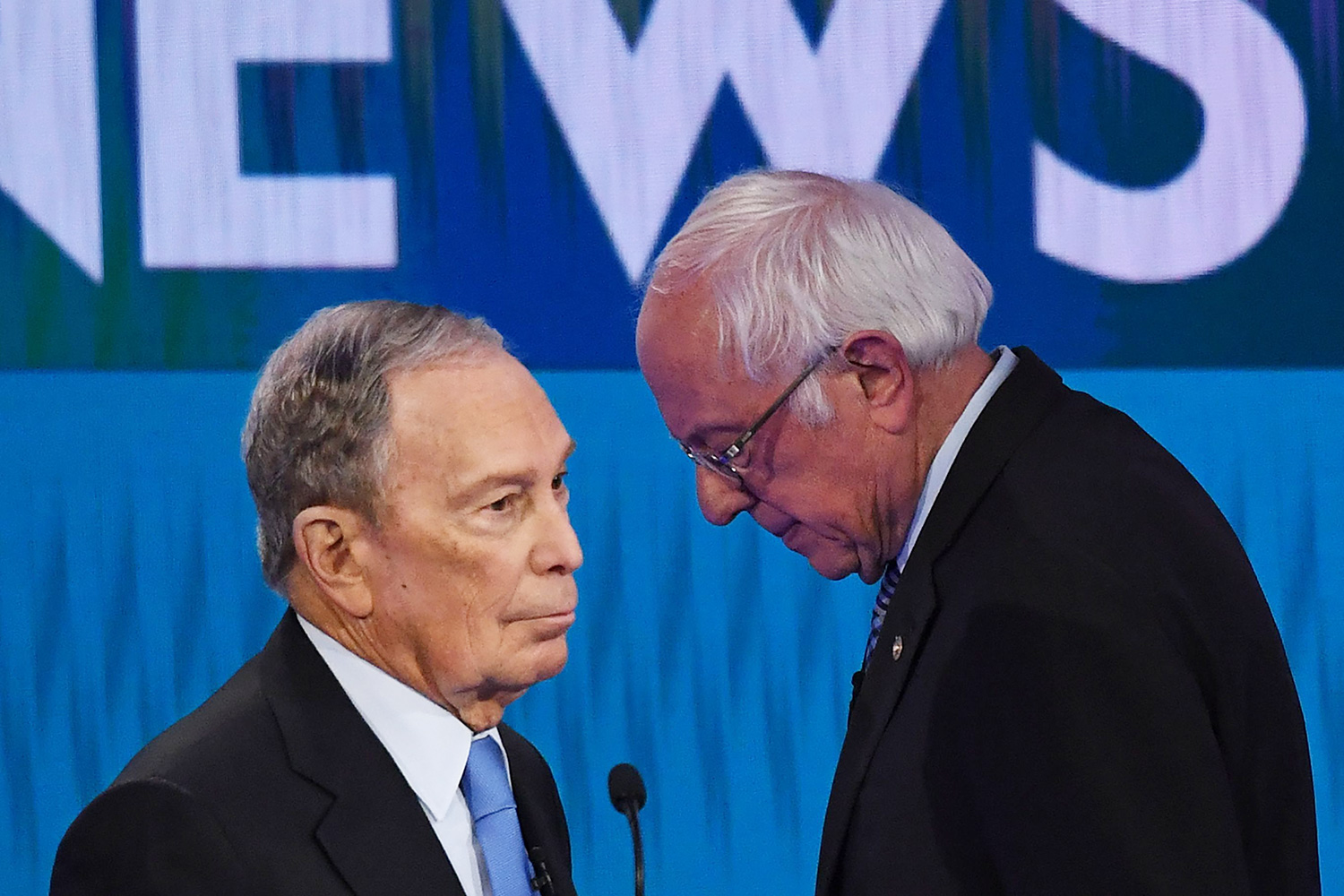 Democratic presidential hopefuls Former New York Mayor Mike Bloomberg (L) and Vermont Senator Bernie Sanders (R) speak during a break in the ninth Democratic primary debate