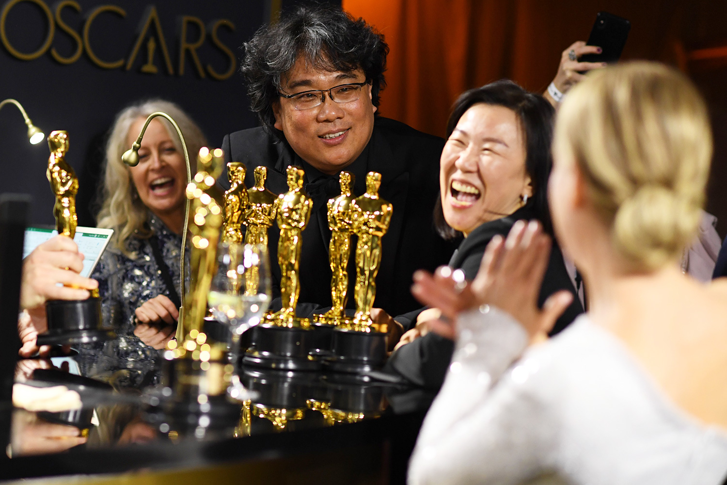 South Korean film director Bong Joon Ho (L), producer Kwak Sin-ae and US actress Renee Zellweger (R) wait for their awards to be engraved as they attend the 92nd Oscars Governors Ball at the Hollywood & Highland Center in Hollywood, California on February 9, 2020.