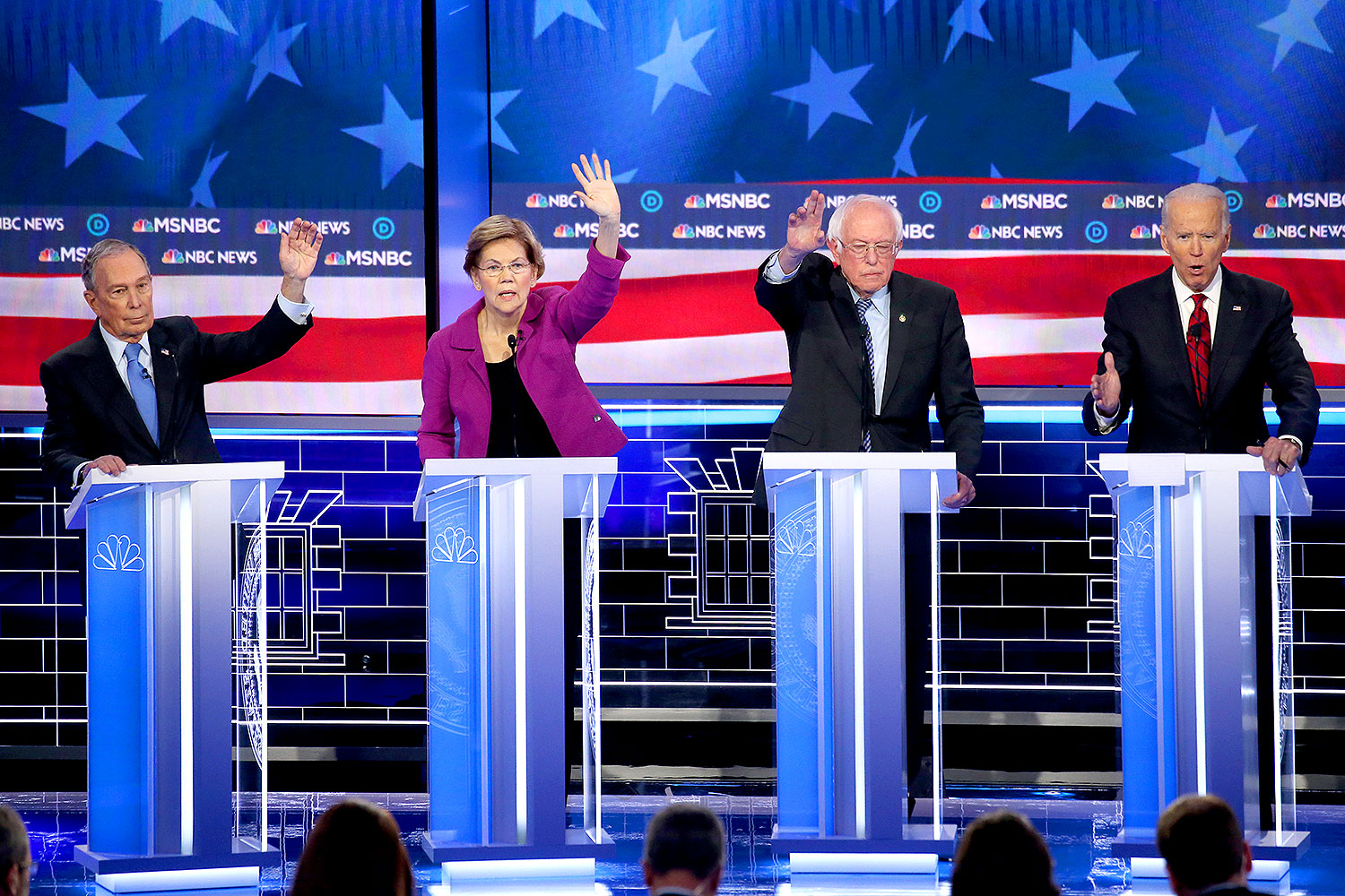 Mike Bloomberg, Sen. Elizabeth Warren (D-MA) and Sen. Bernie Sanders (I-VT) raise their hands as former Vice President Joe Biden