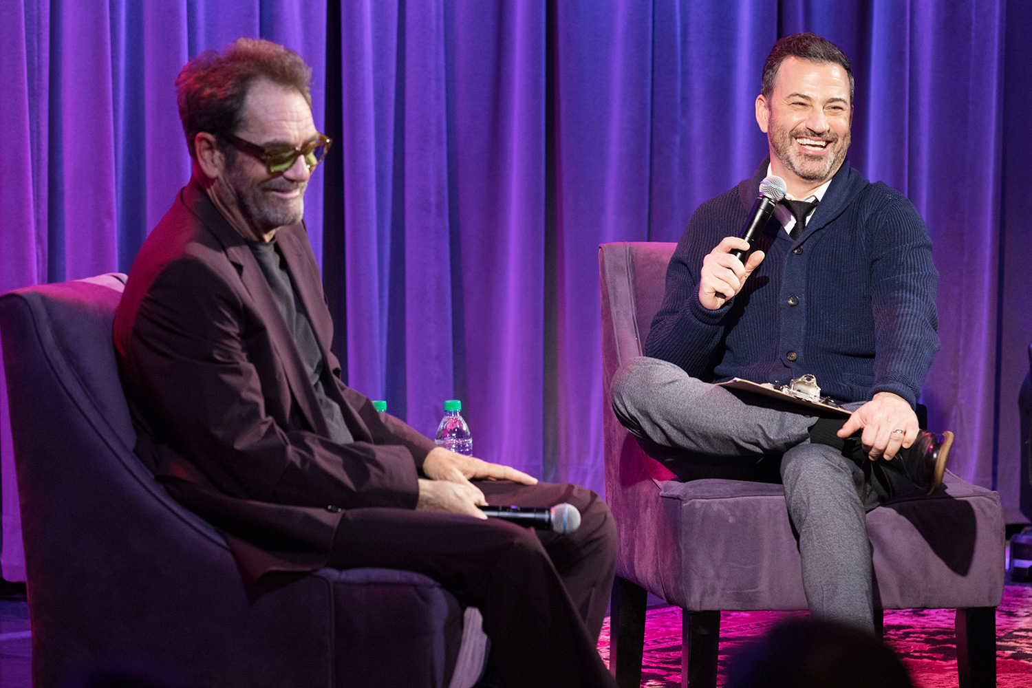 Huey Lewis and Jimmy Kimmel speak onstage during A Conversation With Huey Lewis at The GRAMMY Museum on February 12, 2020 in Los Angeles, California