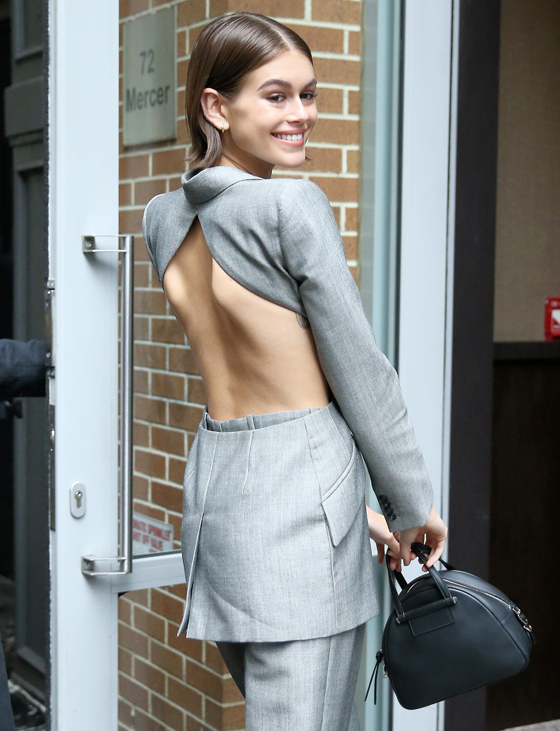Kaia Gerber is seen wearing an open-back silver pants suit after her Jimmy Choo x Kaia appearance in New York City