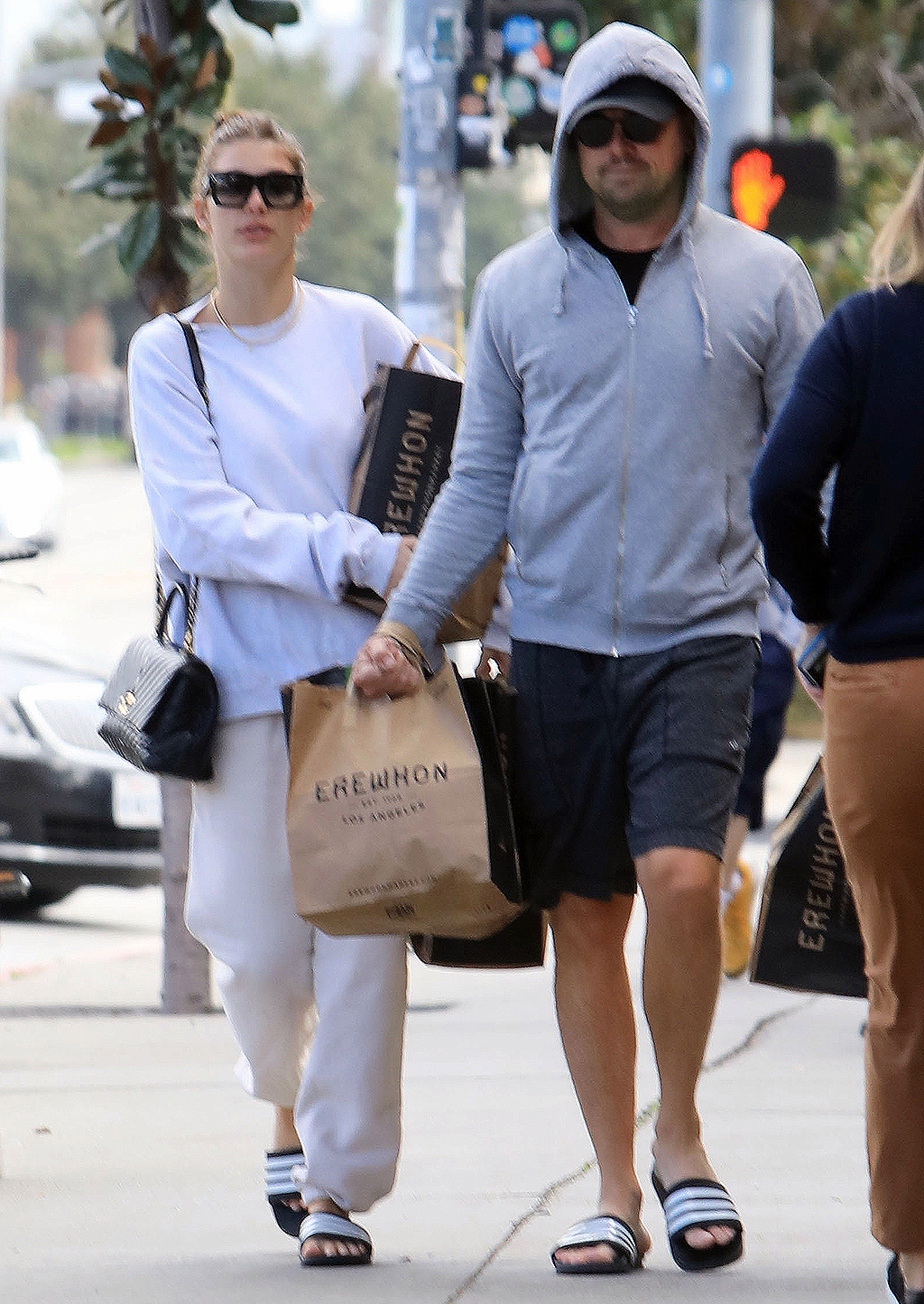 Leonardo DiCaprio and Camila Morrone step out for some grocery shopping in Los Angeles wearing matching slides. DiCaprio, 45, kept a low profile in a baseball cap, grey hoodie, and Alo shorts.