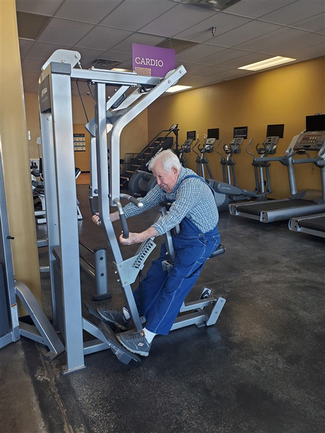 Lloyd Black elderly man works out in overalls
