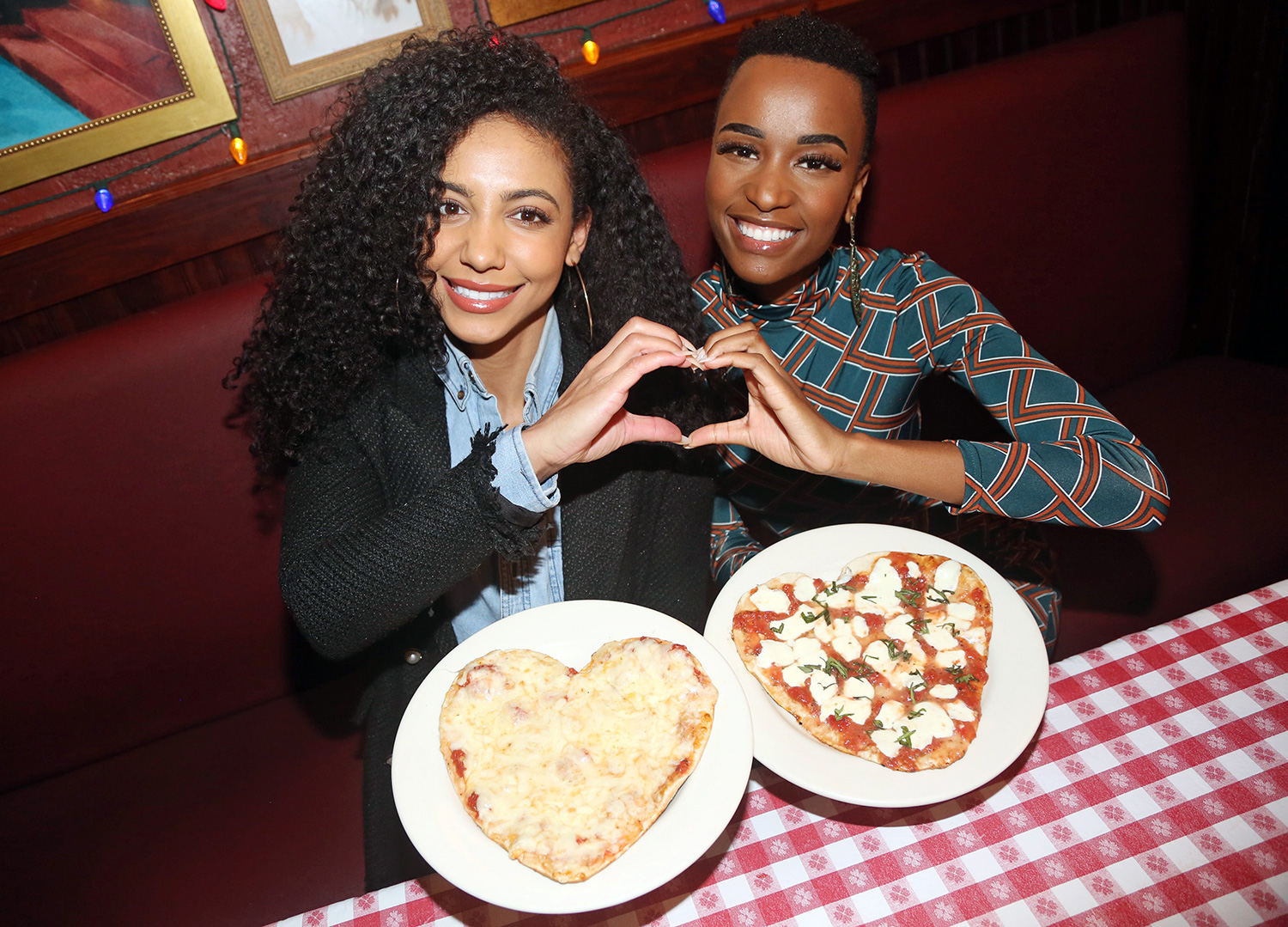 Miss USA 2019 Cheslie Kryst and Miss Universe 2019 Zozibini Tunzi pose as Miss USA & Miss Universe celebrate Valentines Day with Limited Edition Heart Shaped Pizza at Buca di Beppo Times Square on February 5, 2020 in New York City