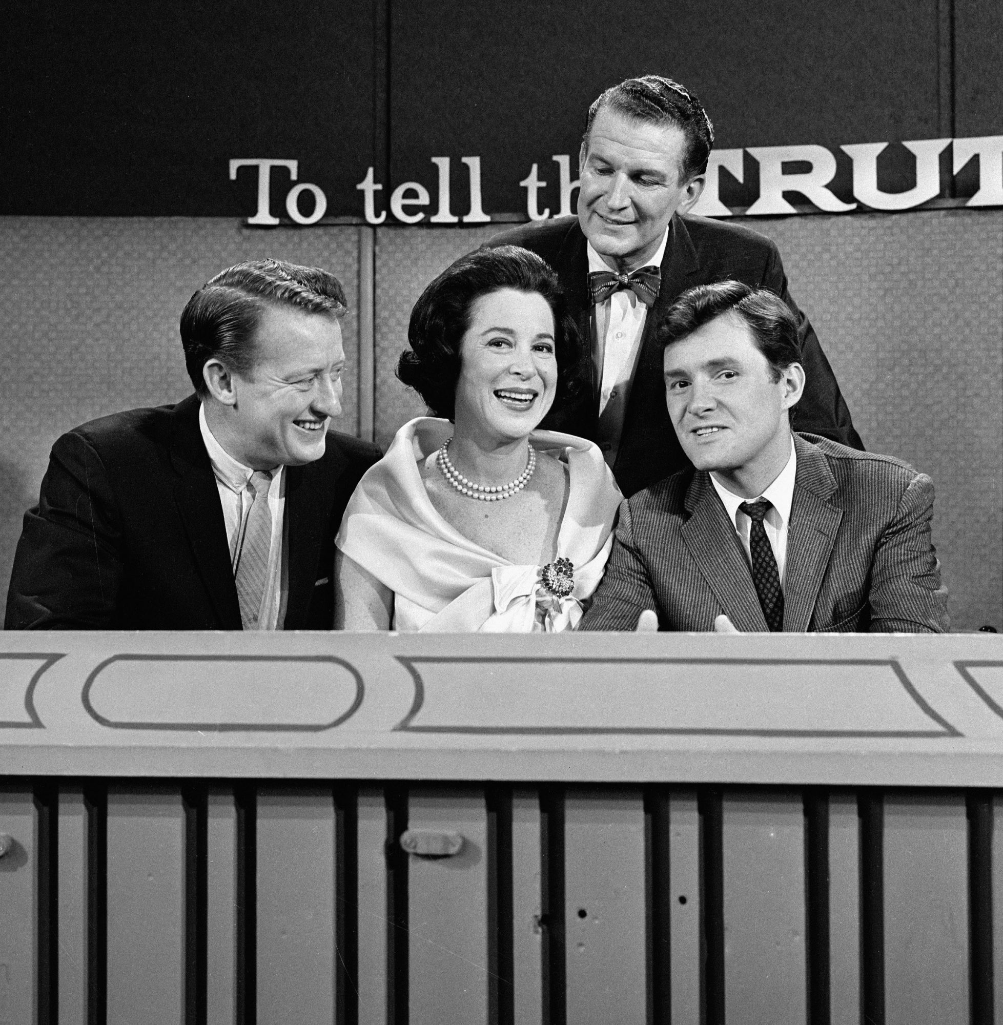 Seated from left, American game show panellists and actors Tom Poston, Kitty Carlisle, and Orson Bean sit with host Bud Collyer (