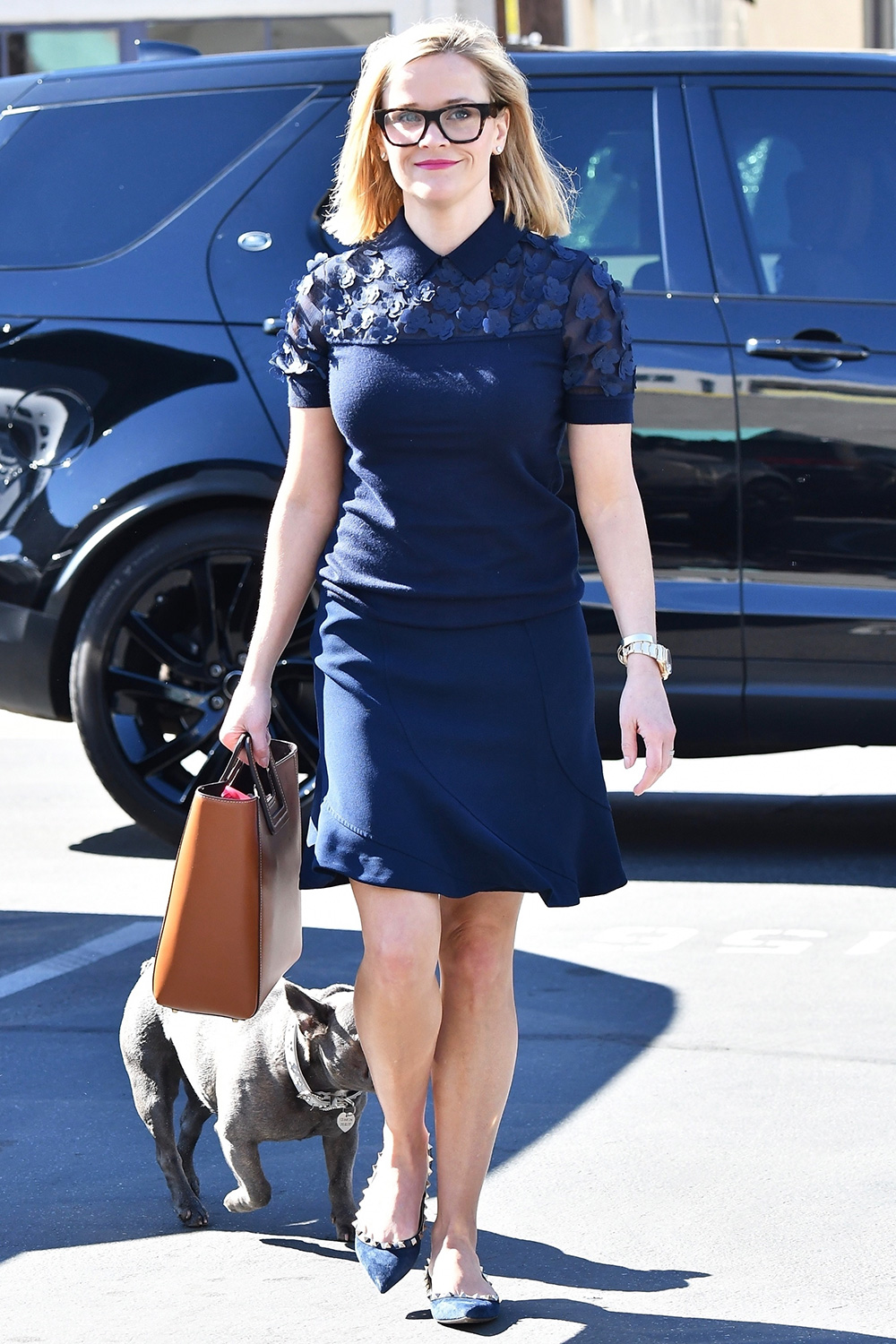 Reese opted for a different look as she is seen wearing black framed glasses with a dark blue dress and matching flats. Reese decided to bring her dog to the office to keep her company.