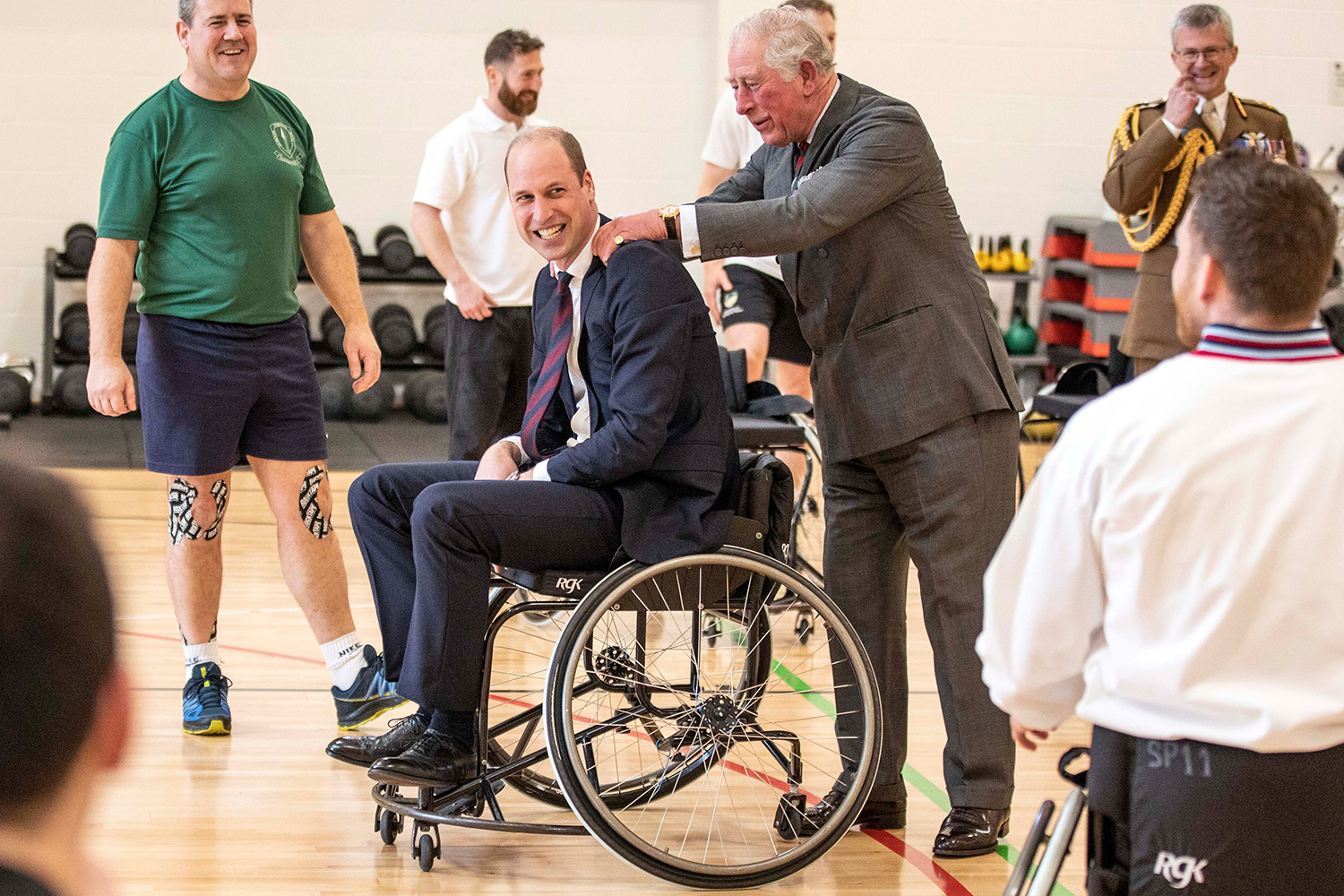 The Duke of Cambridge has his shoulders rubbed by the Prince of Wales after he attempted and failed to throw a basket ball into the hoop while playing wheelchair basket ball during a visit to the Defence Medical Rehabilitation Centre Stanford Hall, Stanford on Soar, Loughborough, where they met with patients and staff and had a tour of the gym and prosthetics workshop.
