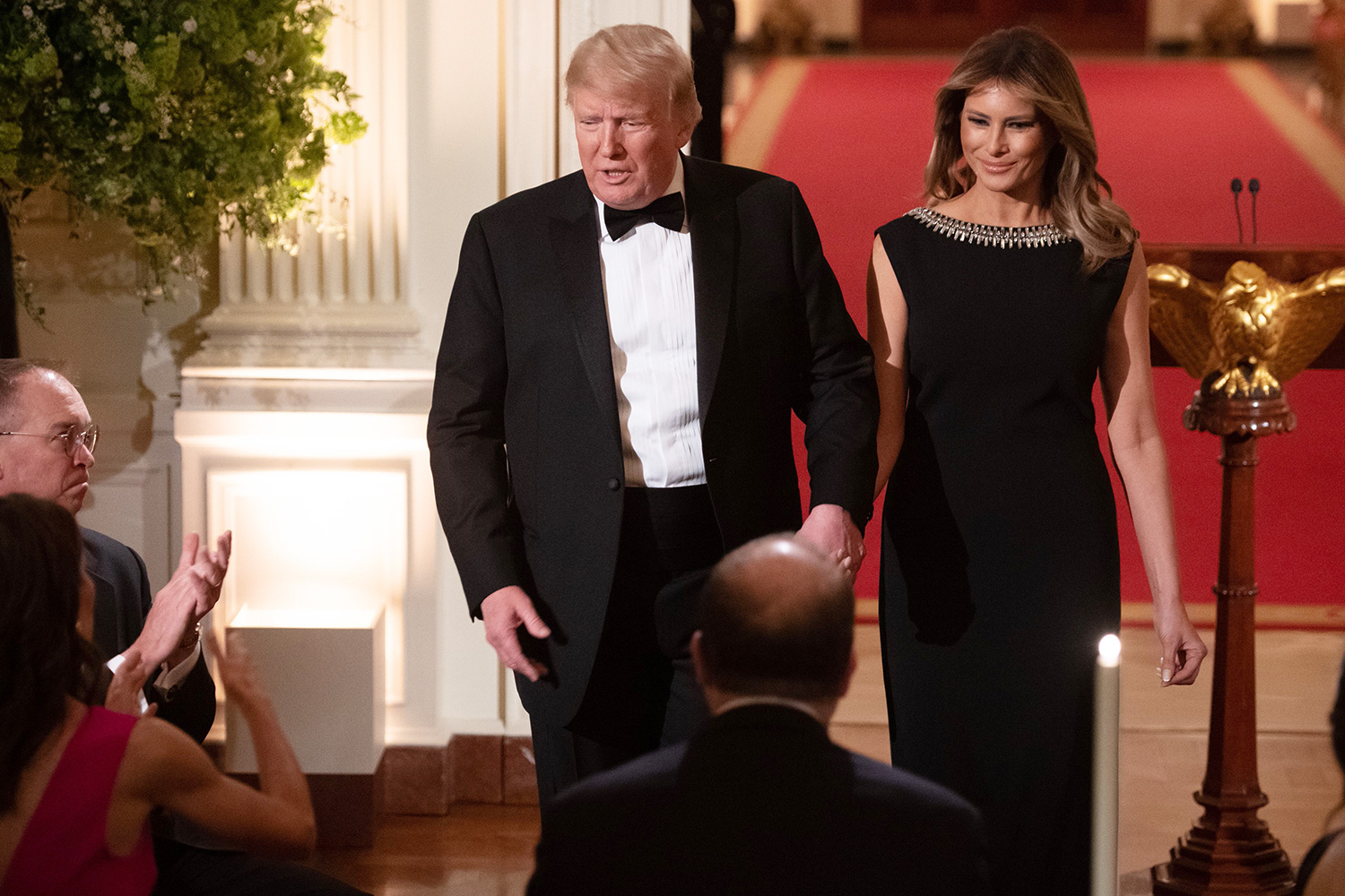 US President Donald Trump speaks alongside First Lady Melania Trump as they host the Governors' Ball in the East Room of the White House in Washington, DC, February 9, 2020