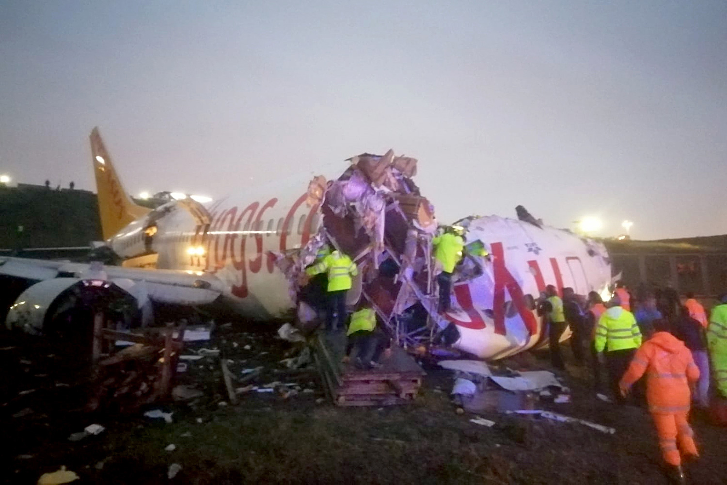 Officials work around the site after a passenger plane skidded off the runway in Istanbul Sabiha Gokcen International Airport, breaking into two, on February 05, 2020 in Istanbul, Turkey. Several firefighters and paramedics were dispatched to the area