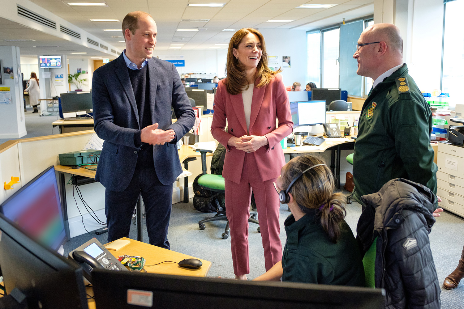 Palace of the Duke and Duchess of Cambridge talking with Chief Executive of the London Ambulance Service, Garrett Emmerson, and an unidentified staff member (left) during a visit to the London Ambulance Service 111 control room in Croydon on Thursday to meet ambulance staff and 111 call handlers who have been taking NHS 111 calls from the public, and thank them for the vital work they are doing.