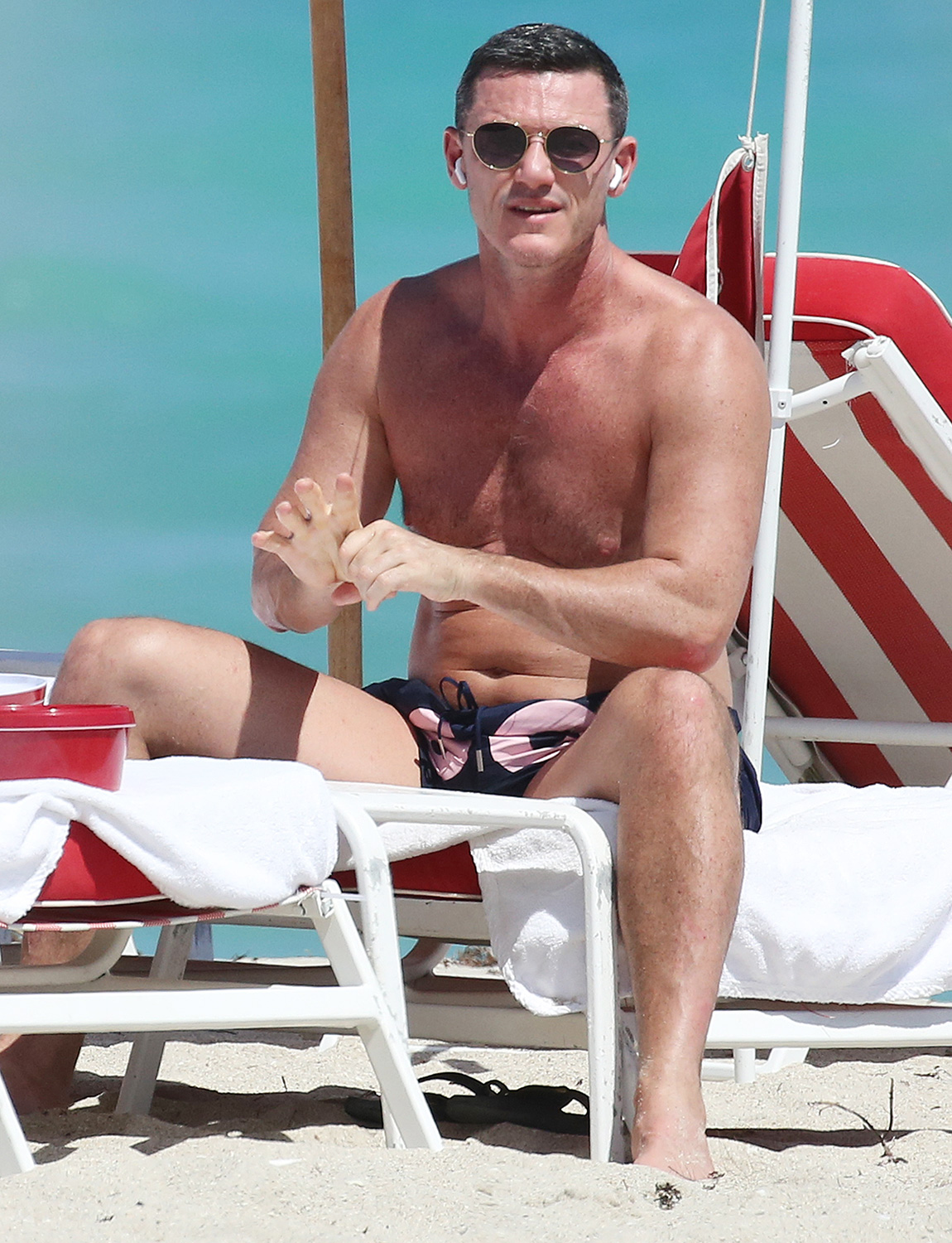 Luke Evans puffs on a Juul as he enjoys a final day of sunshine one day before Miami will close all beaches due to coronavirus