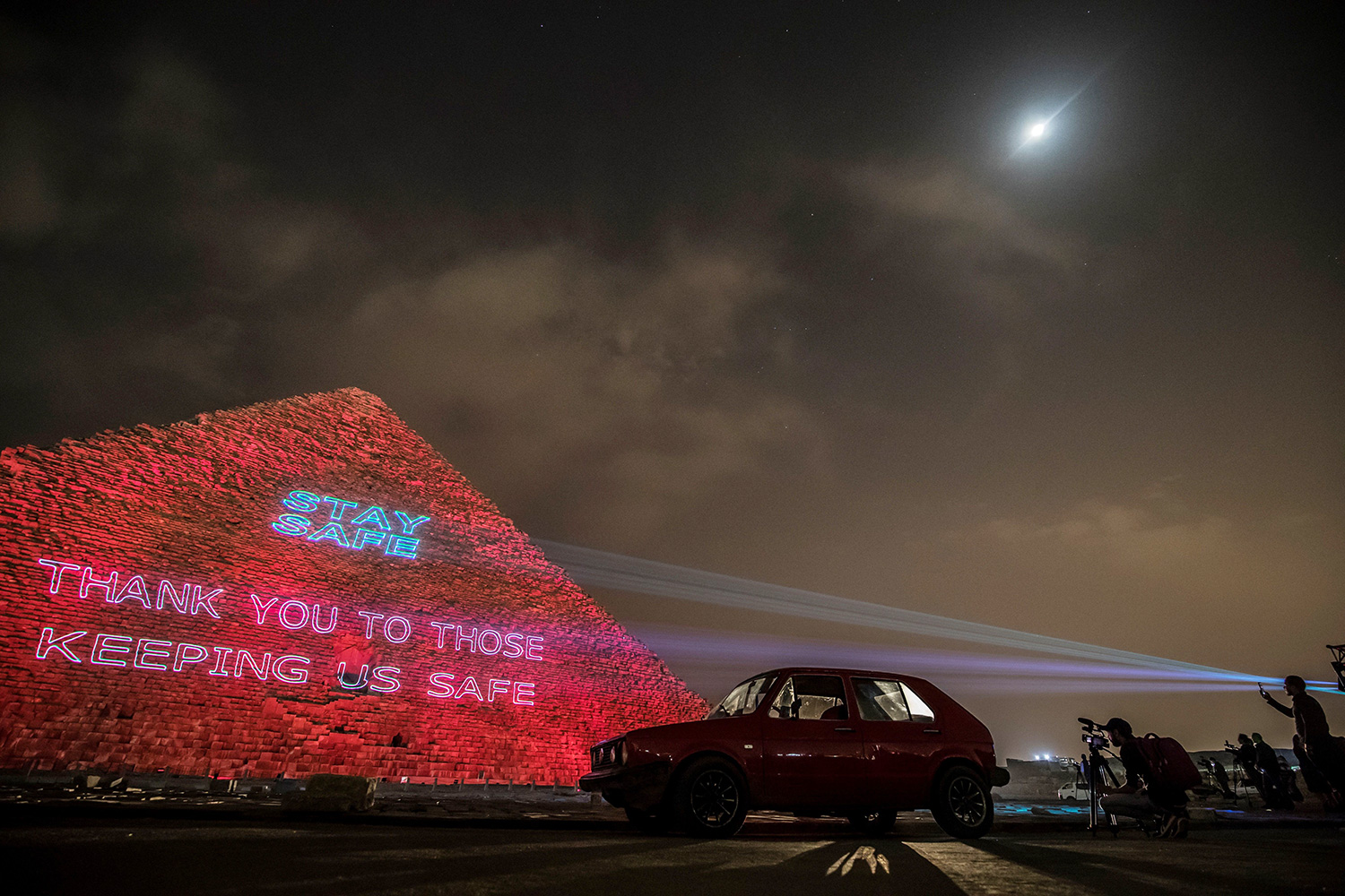 "People take pictures of the Great pyramid of Kheops at the Giza plateau outside the Egyptian capital Cairo where a laser projection writes ""Stay home, thanks to those keeping us safe"" on March 30, 2020, amid the spread of the COVID-19 infection"