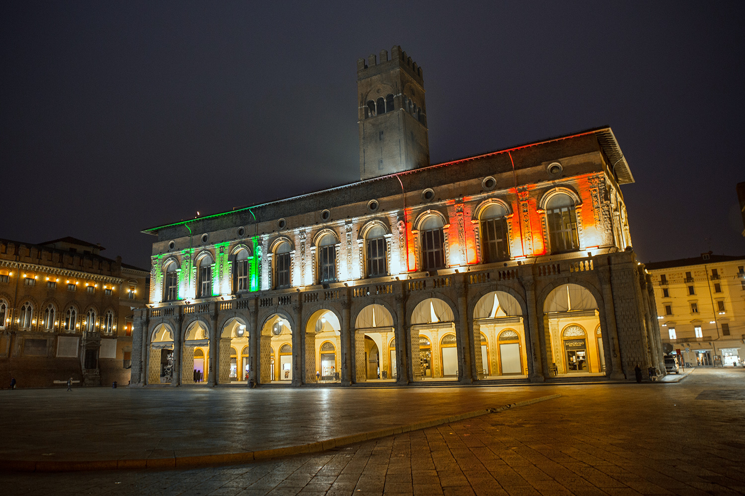Piazza Maggiore, Palazzo Re Enzo is lit with the Italian's flag colors on March 27, 2020 in Bologna, Italy