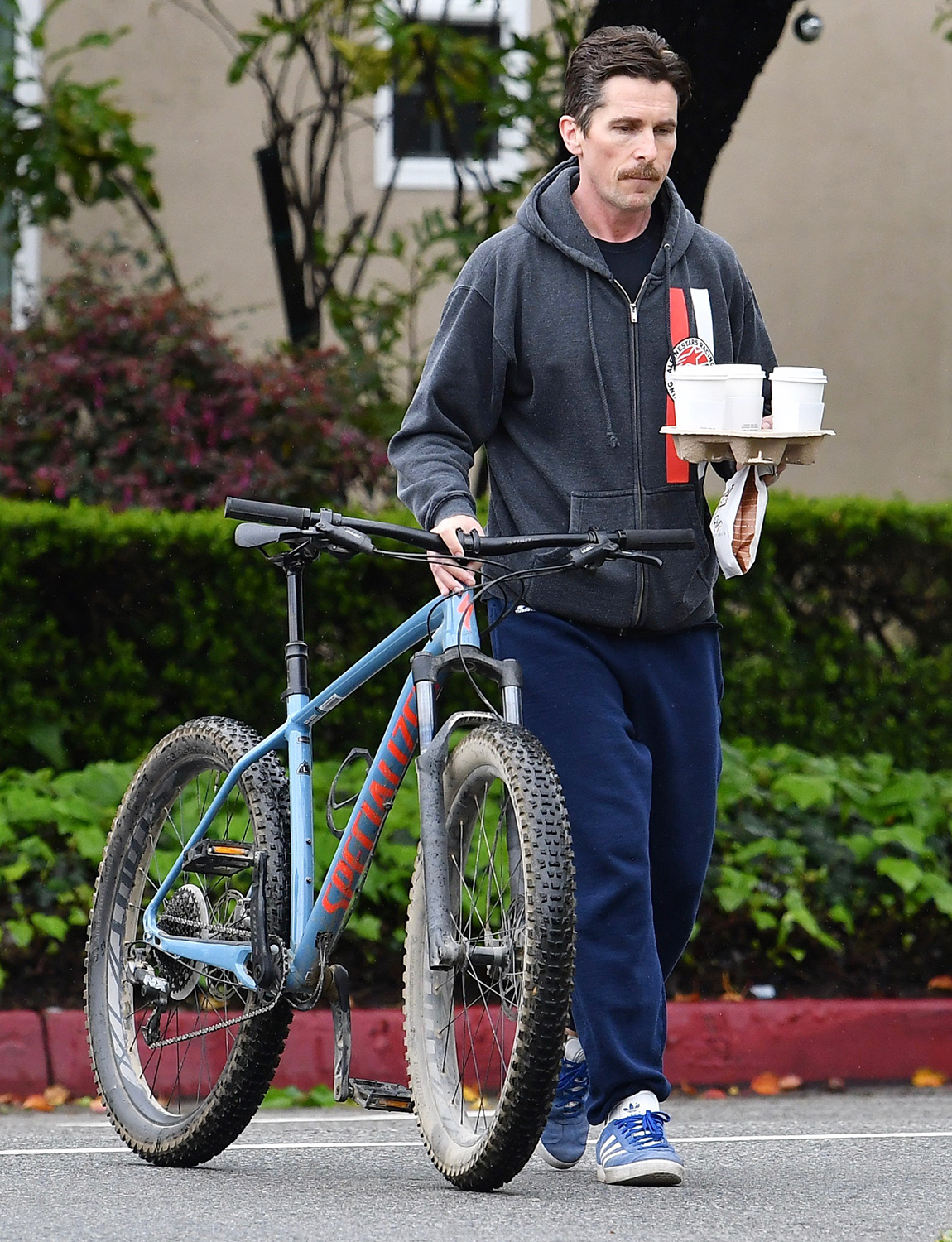 Christian Bale picking up three coffee and a pastry With is bicycle on a rainy day.