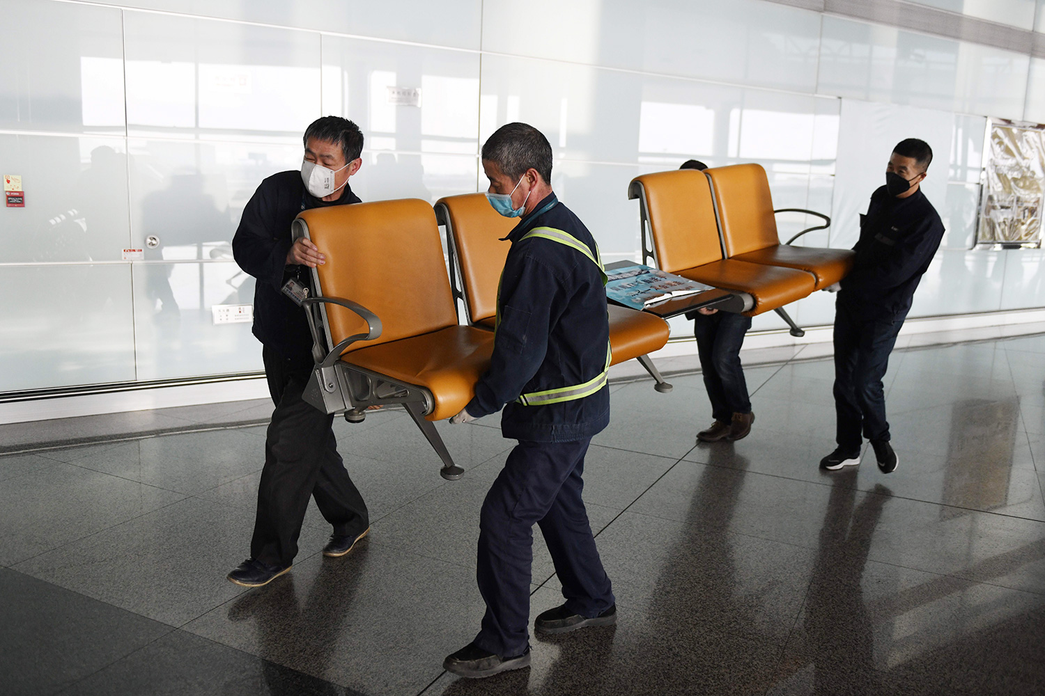Workers wear face masks as they remove seating from a public area at the Beijing Capital Airport in Beijing on March 5, 2020