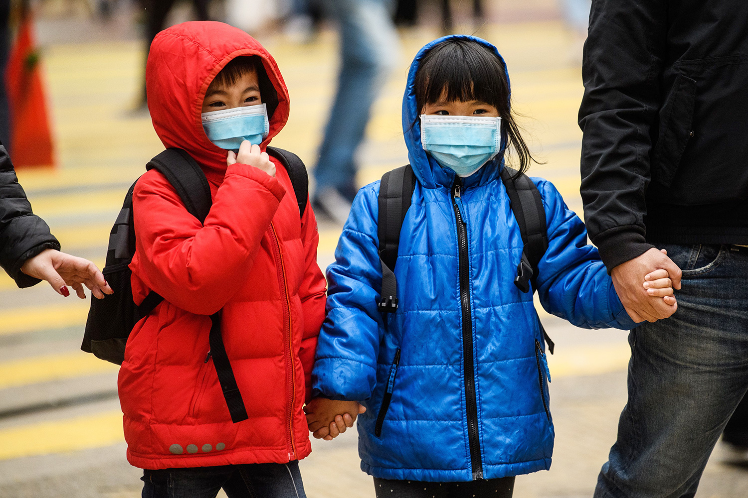 Children wearing face masks cross a road during a Lunar New Year of the Rat public holiday in Hong Kong on January 27, 2020