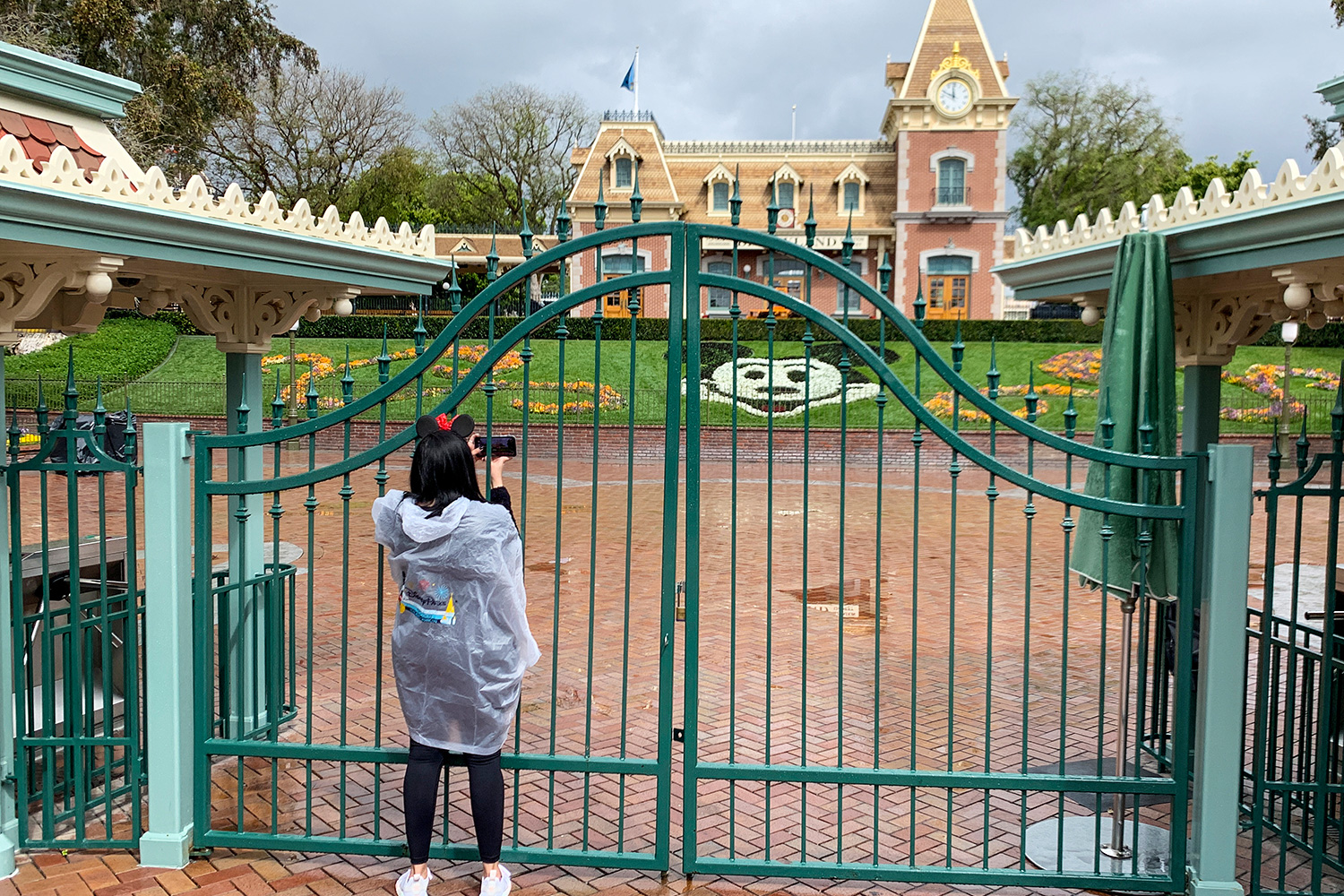 A visitor to the Disneyland Resort takes a picture through a locked gate at the entrance to Disneyland in Anaheim, CA, on Monday, Mar 16, 2020