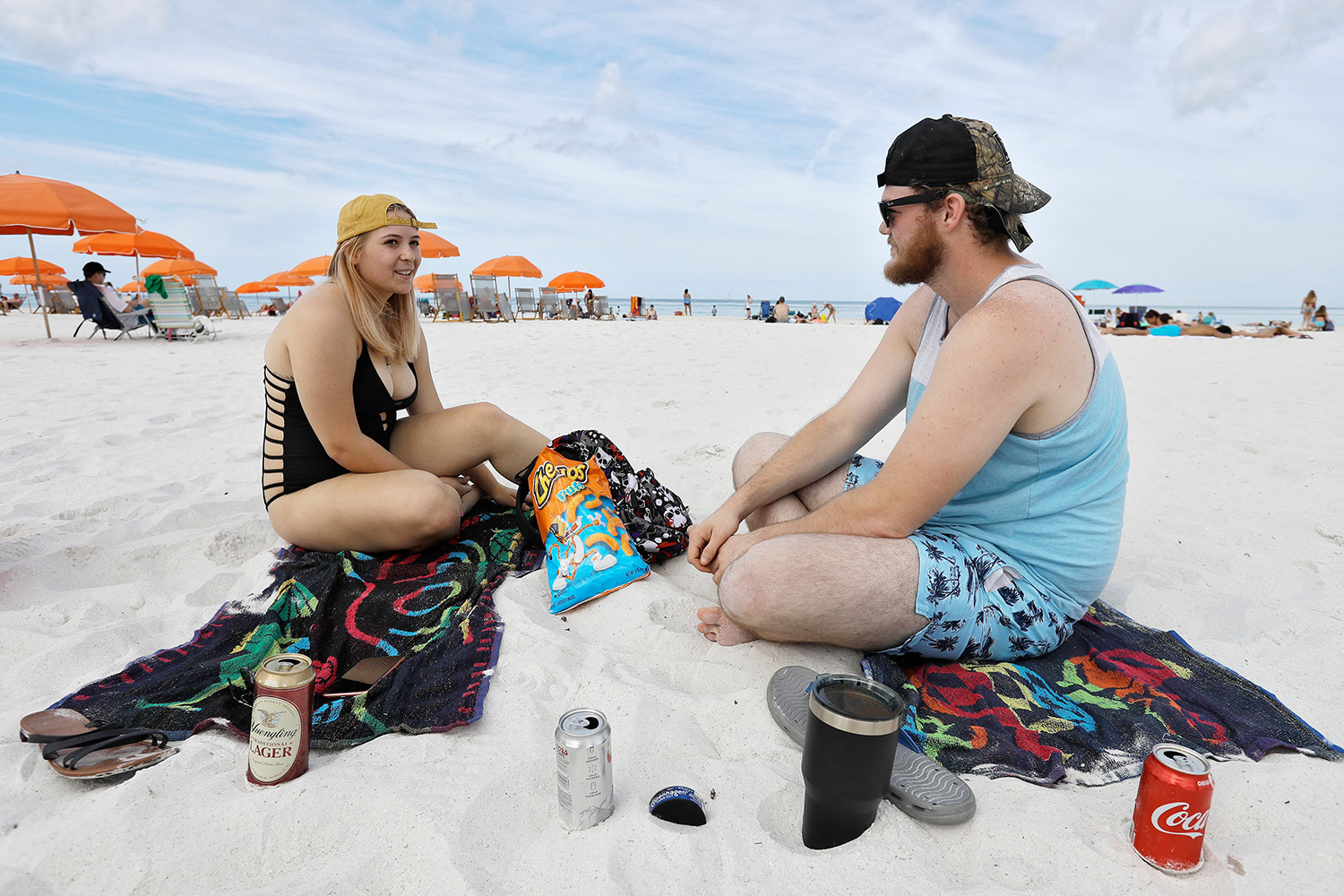 Students Erin West, left, of Wesley Chapel, Fla., and Jessie Wilcox, of Charleston, W.V., talk as they sit on North Beach, in Clearwater Beach, Fla. Beach goers are keeping a safe distance as they enjoy the Florida weather Virus Outbreak Florida Beaches, Clearwater Beach, United States - 17 Mar 2020