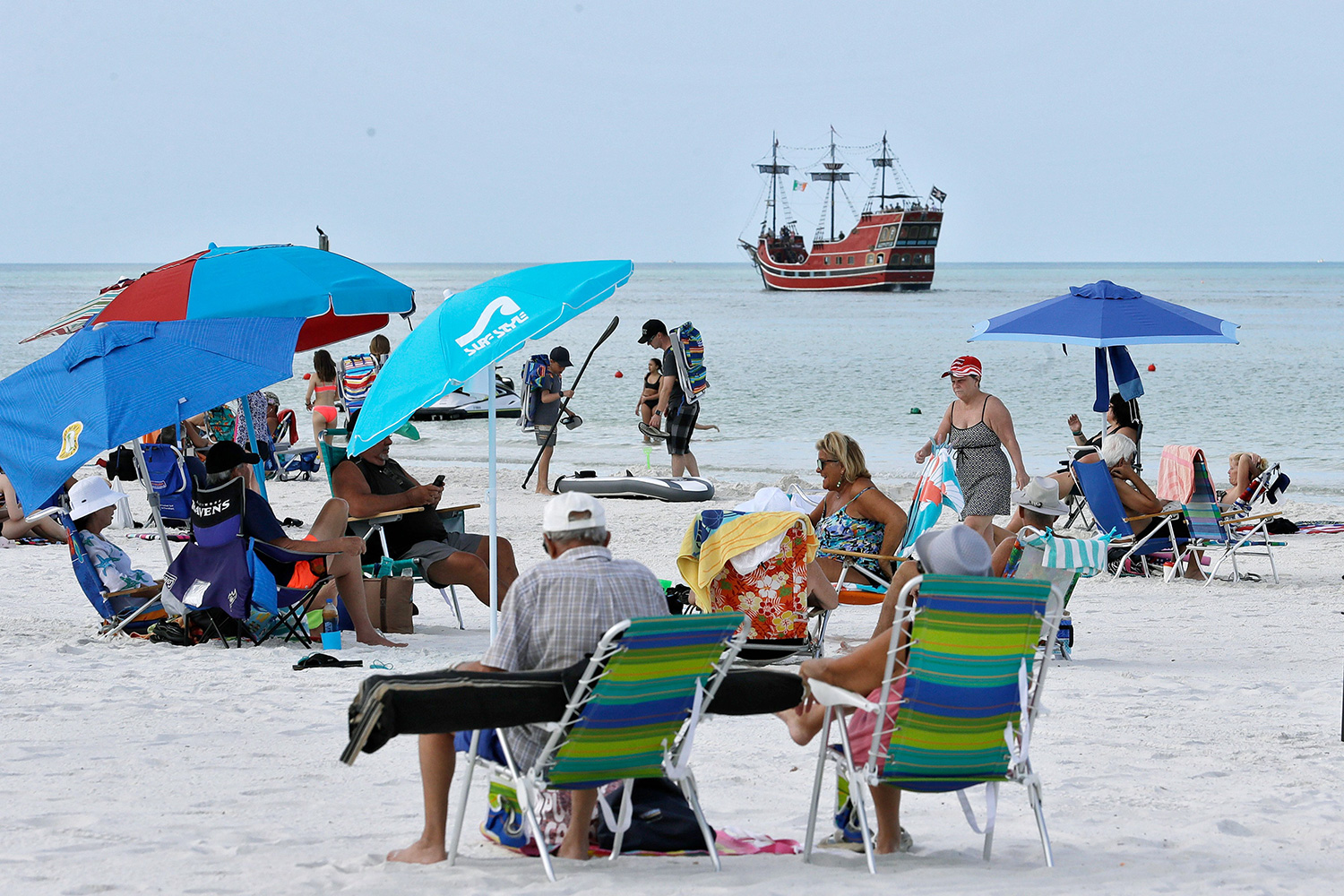Visitors sit on the North Beach, in Clearwater Beach, Fla. Beach goers are keeping a safe distance to avoid the spread of the coronavirus as they enjoy the Florida weather Virus Outbreak Florida Beaches, Clearwater Beach, United States - 17 Mar 2020