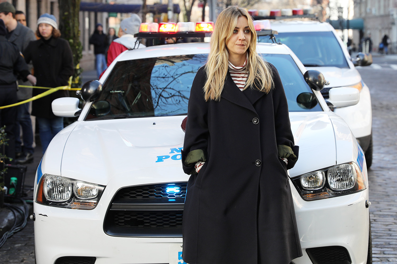"""Kaley Cuoco pictured drinking vodka from a tiny bottle as she leans in front of a police car during a scene at """"The Flight Attendant"""" set in Downtown, Manhattan"""