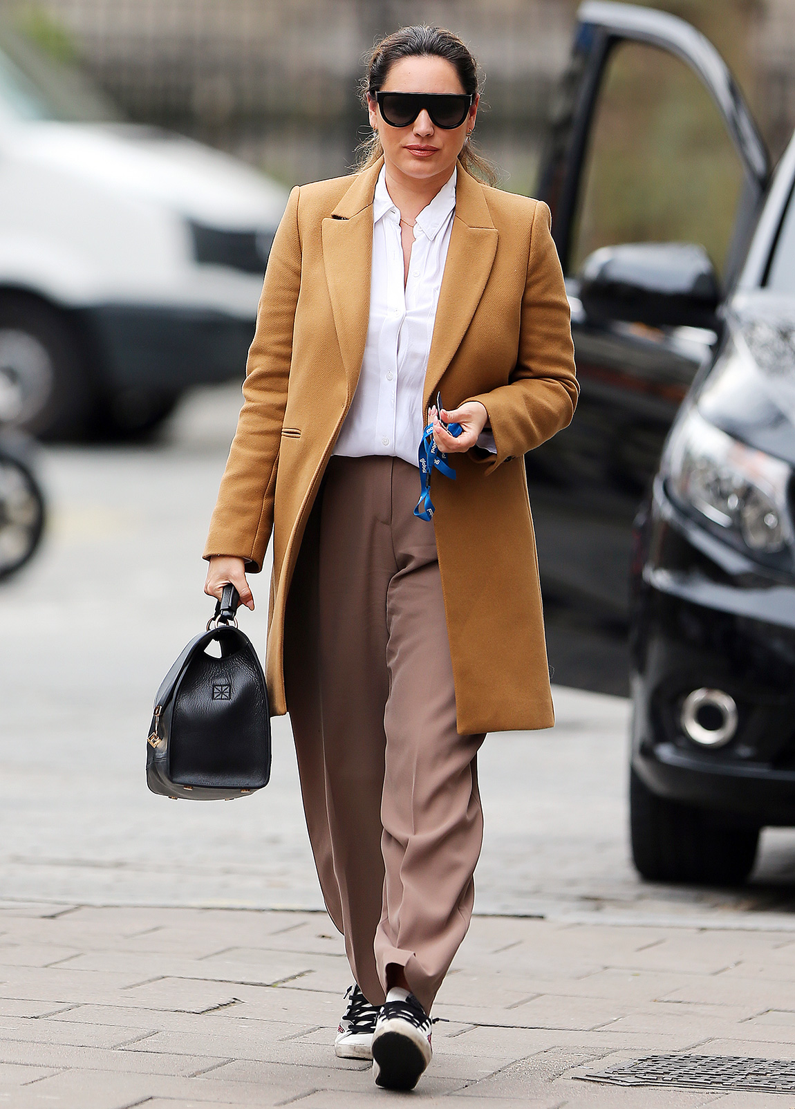 Kelly Brook wearing a long beige coat, white shirt, brown trousers and a pair of trainers arriving at Heart FM in London.