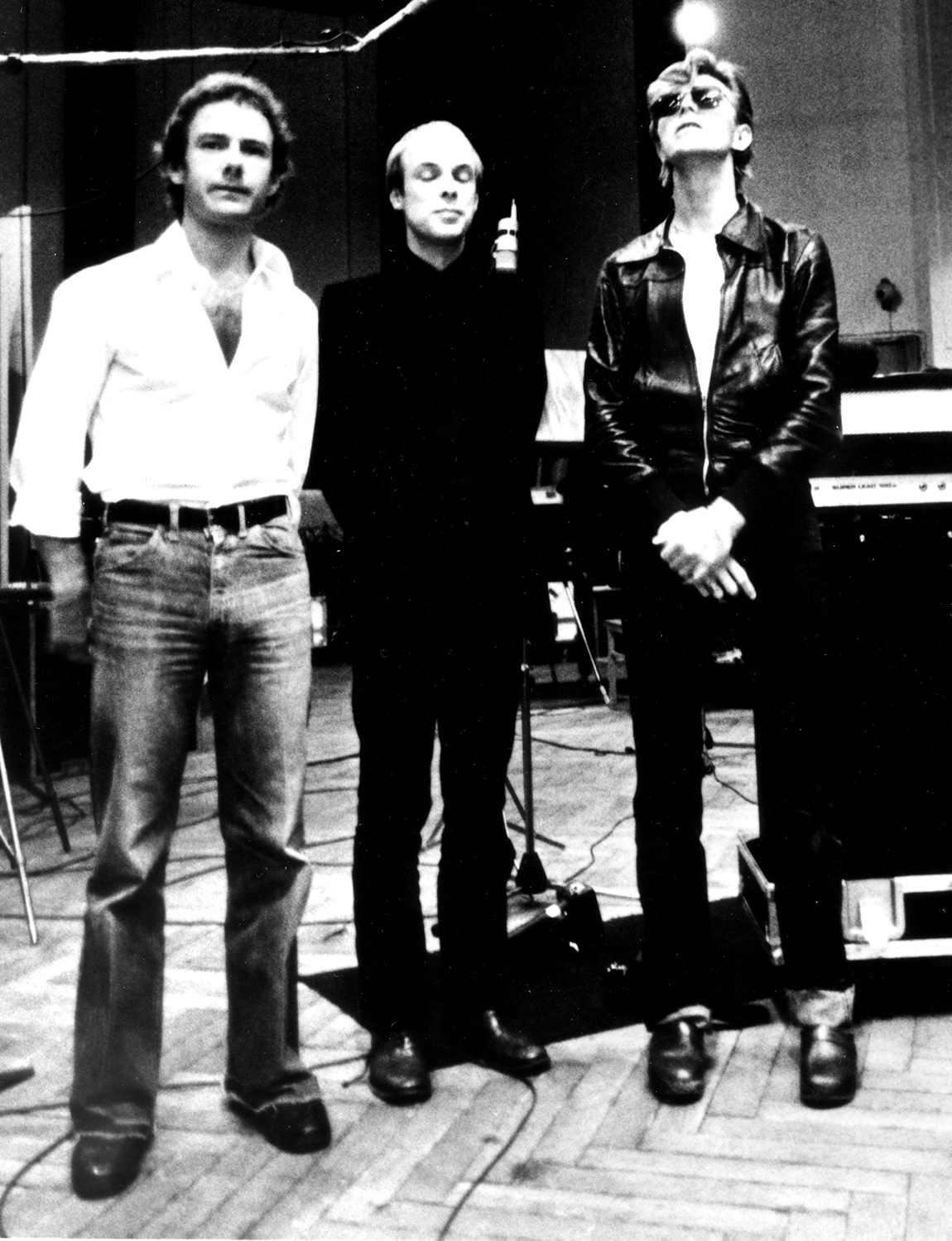 """Robert Fripp, Brian Eno and David Bowie pose for a portrait in the studio where they are recorded """"Heroes"""" in 1977 in Berlin, Germany"""