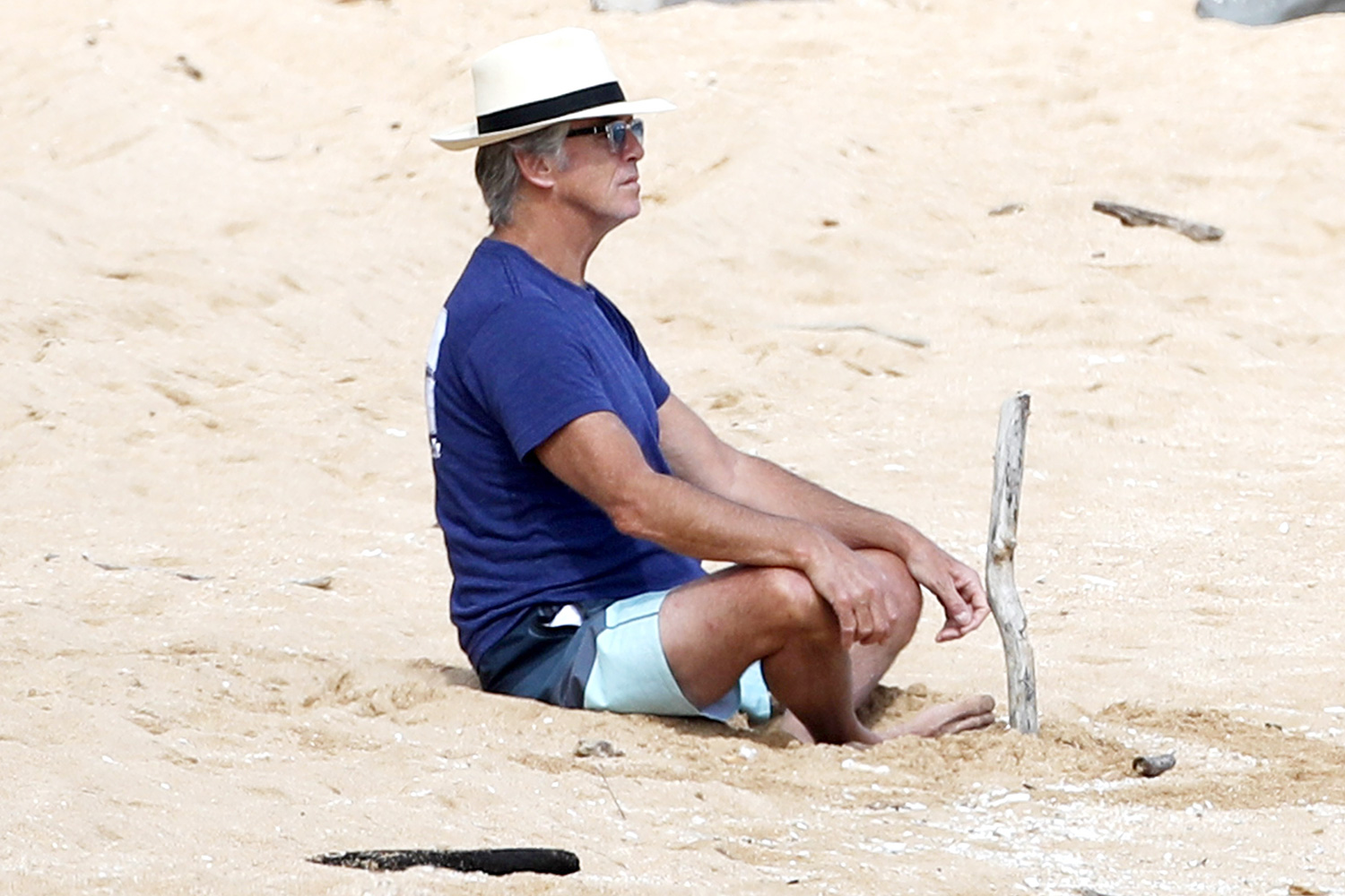 Pierce Brosnan takes a moment to meditate on the beach in Hawaii