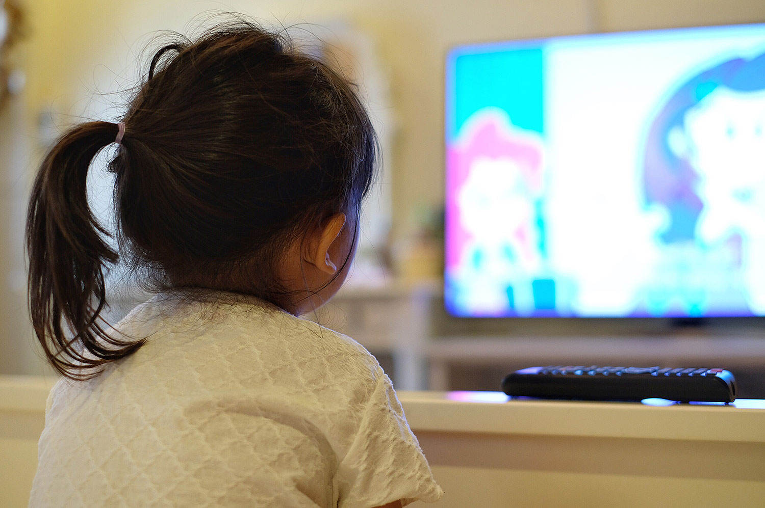Rear View Of Girl Watching Tv