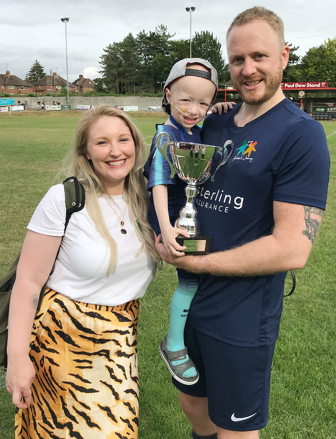 Archie Wilks holding the trophy with his parents Simon and Harriet following a charity football match in Saffron Walden, Essex