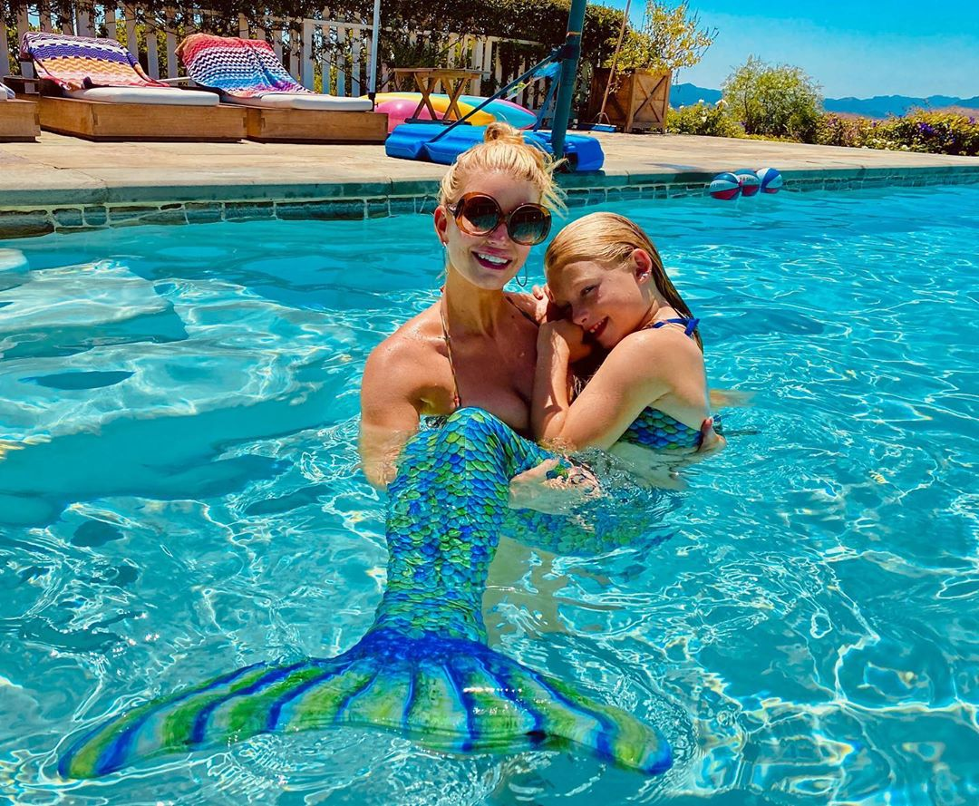"""The """"Open Book"""" author shared a summertime snap of her and her daughter, Maxwell, 8, hanging out in the backyard pool.                             And, of course, no pool date is complete without a little mermaid magic! """"Me and Maximaid,"""" Simpson captioned the photo."""