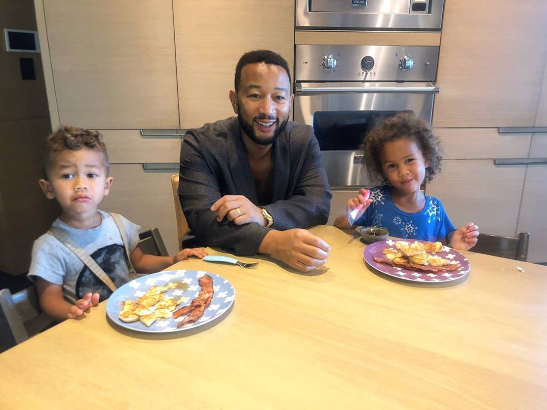 """""""I make pancakes every Sunday,"""" the """"All of Me"""" singer captioned this sweet photo of himself with his two kids - Miles, 2, and Luna, 4, who he shares with his wife, Chrissy Teigen - eating breakfast in the kitchen. The couple recently announced they are expecting a third child.                              """"Regardless of this pic, Miles really enjoyed them,"""" Legend joked."""