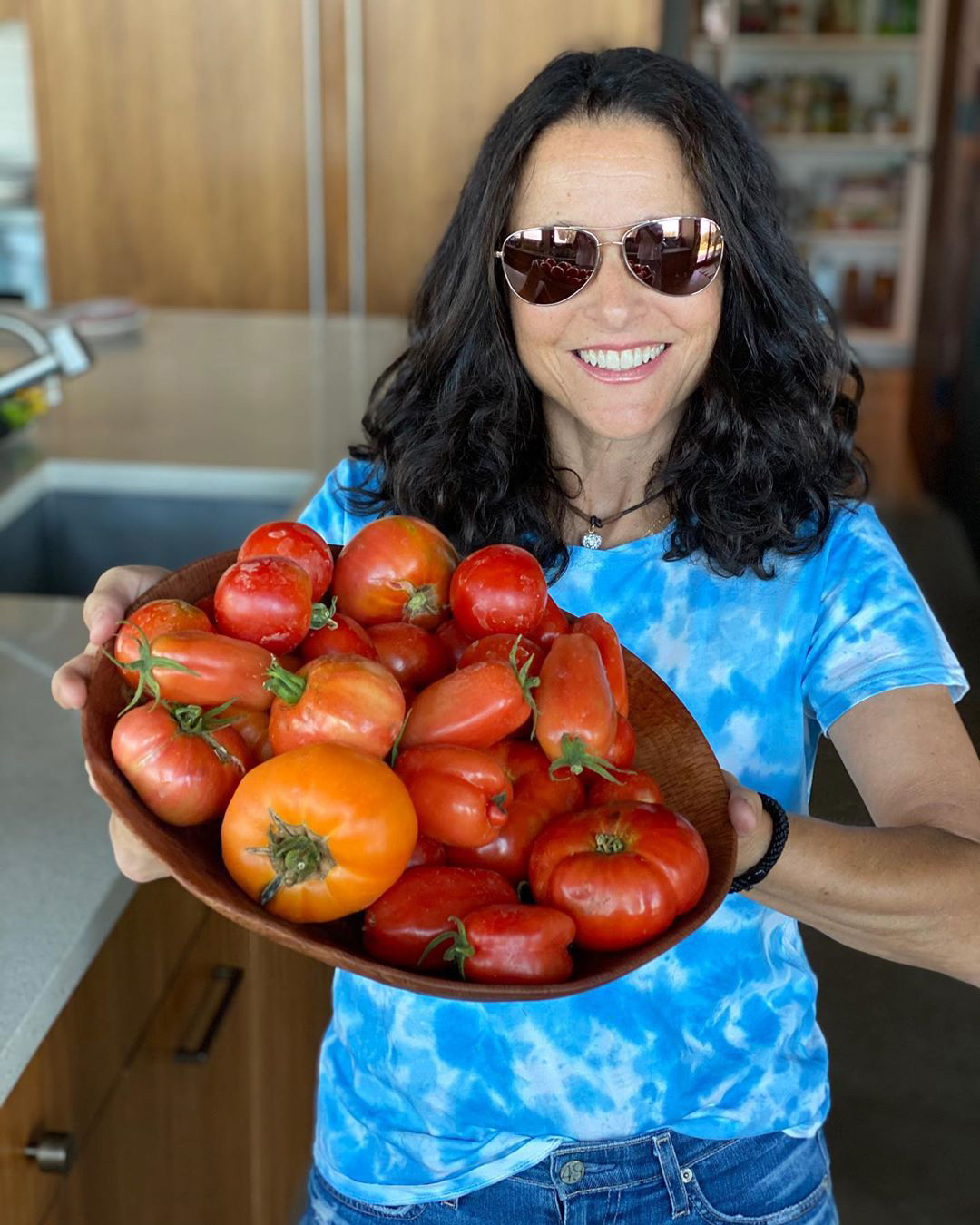 """""""You say tomato and I say a s-t ton,"""" joked the Veep star, holding up a heaping plate of the homegrown fruits in her kitchen.                             """"Better Homes and Gardens magazine's cover this month is 100 best tomato recipes ♥️,"""" Chrissy Teigen shared in the comments section, to which Louis-Dreyfus replied, """"will purchase STAT."""""""