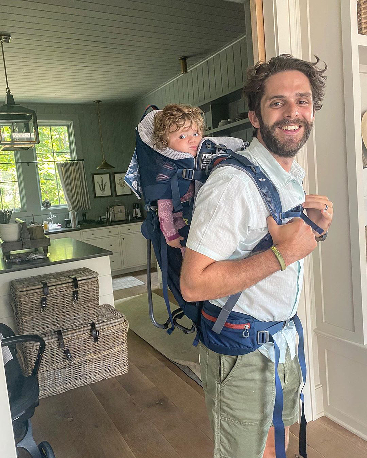 """That face says it all!                             """"Whatever calms them down 😂,"""" joked the country singer, carrying his youngest daughter, Lennon Love, 5 months, on his back in a baby carrier while hanging out in their country-chic kitchen.                             Rhett and his wife, Lauren Akins, also share Willa Gray, 4, and Ada James, 2."""