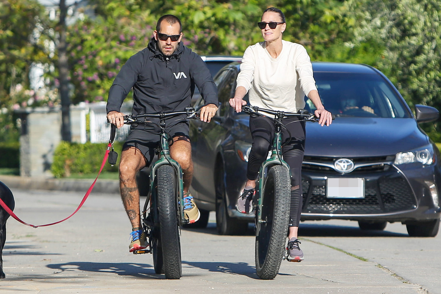 Robin Wright and Clement Giraudet are seen riding bicycles with their dog walking alongside on April 21, 2020 in Los Angeles, California