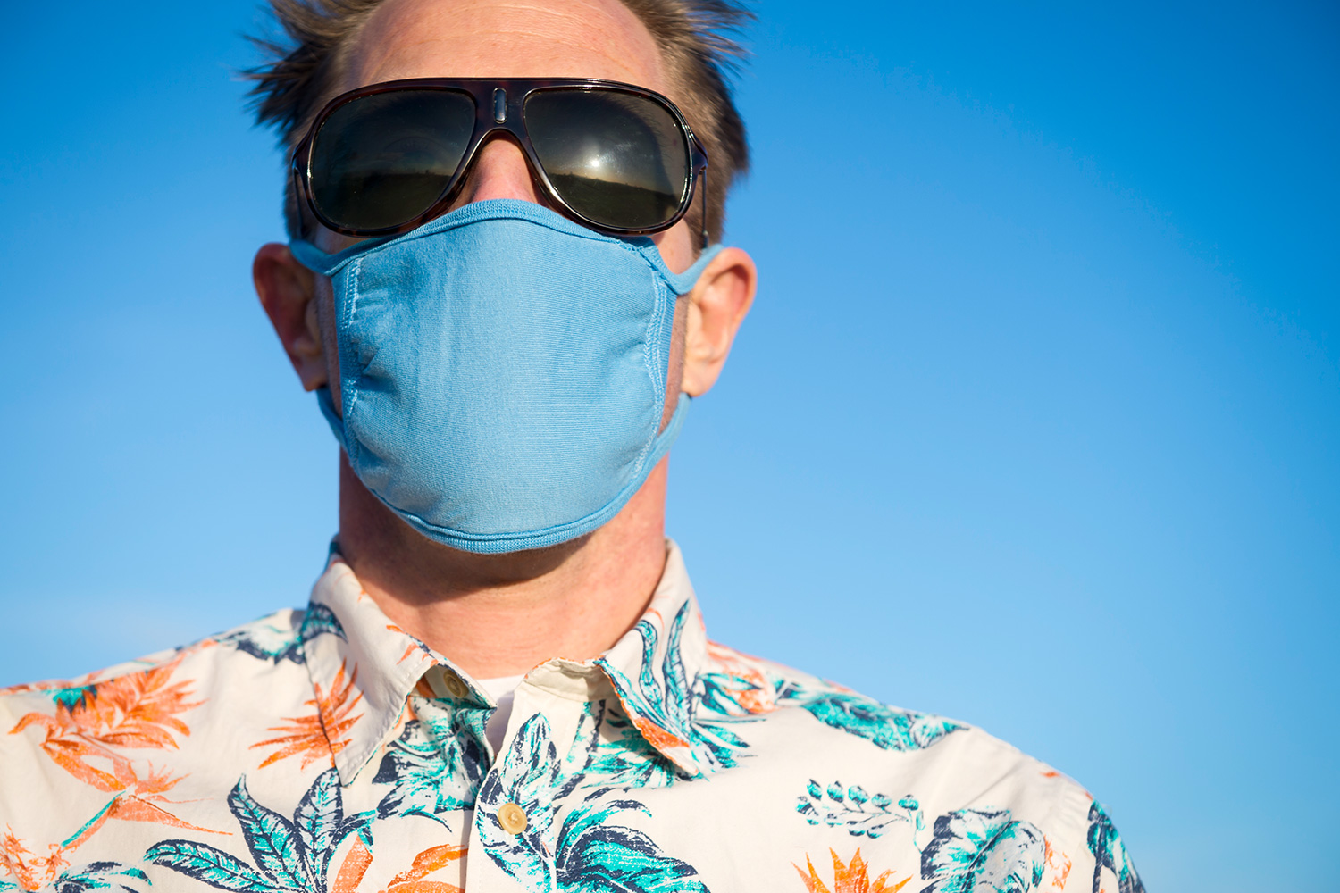 Close up portrait of a man in colorful Hawaiian shirt and sunglasses wearing protective surgical face mask standing outdoors under sunny blue sky