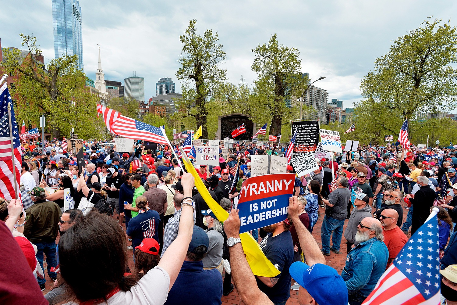 Protesters rally, to demand an end to the state wide 'stay at home advisory' and the new law enforcing everyone to wear a mask in public, outside the Massachusetts State House in Boston, Massachusetts on May 4, 2020