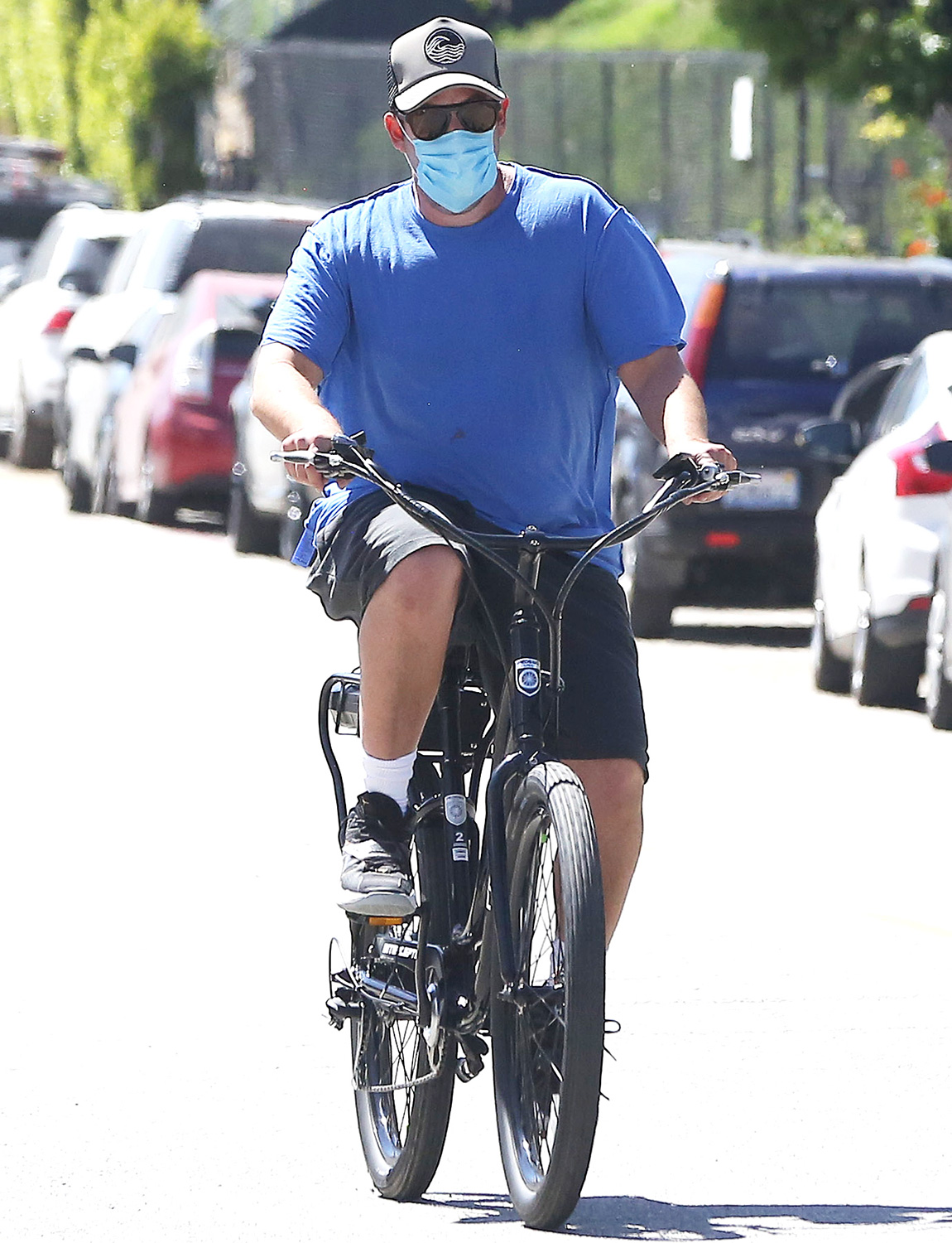 Adam Sandler rides his bike with no mask then goes back home and comes out with a mask on. 05 May 2020