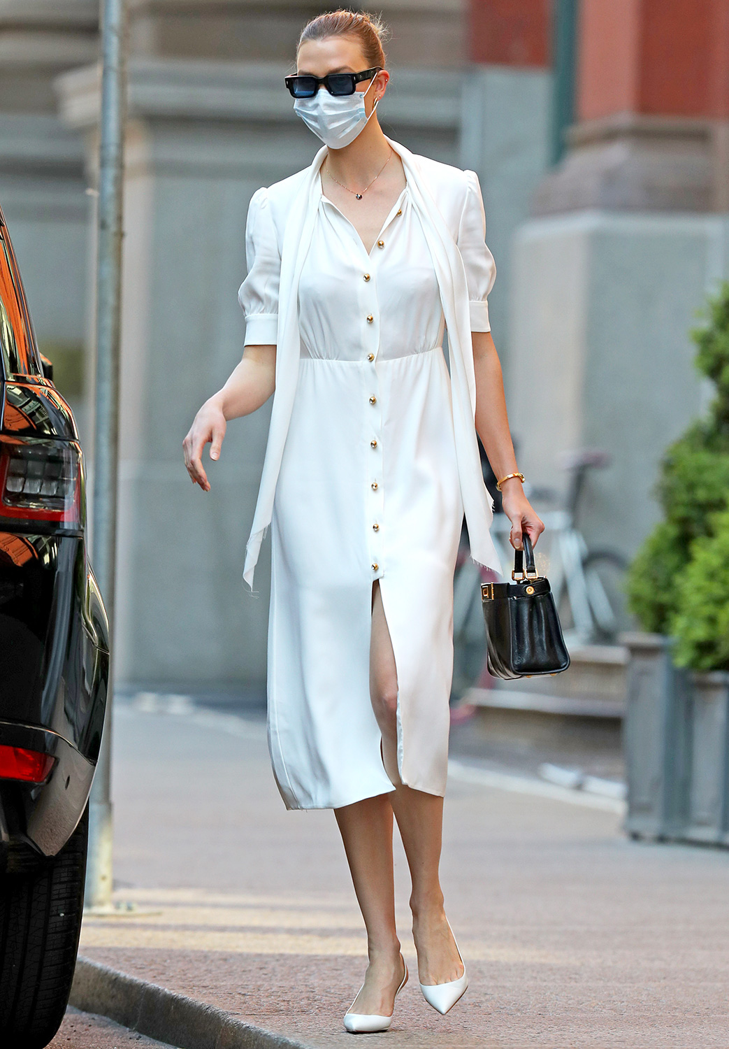 Karlie Kloss is pictured stepping out in New York City. The 27 year old supermodel carried a black handbag and wore a face mask, white dress, and matching heels.