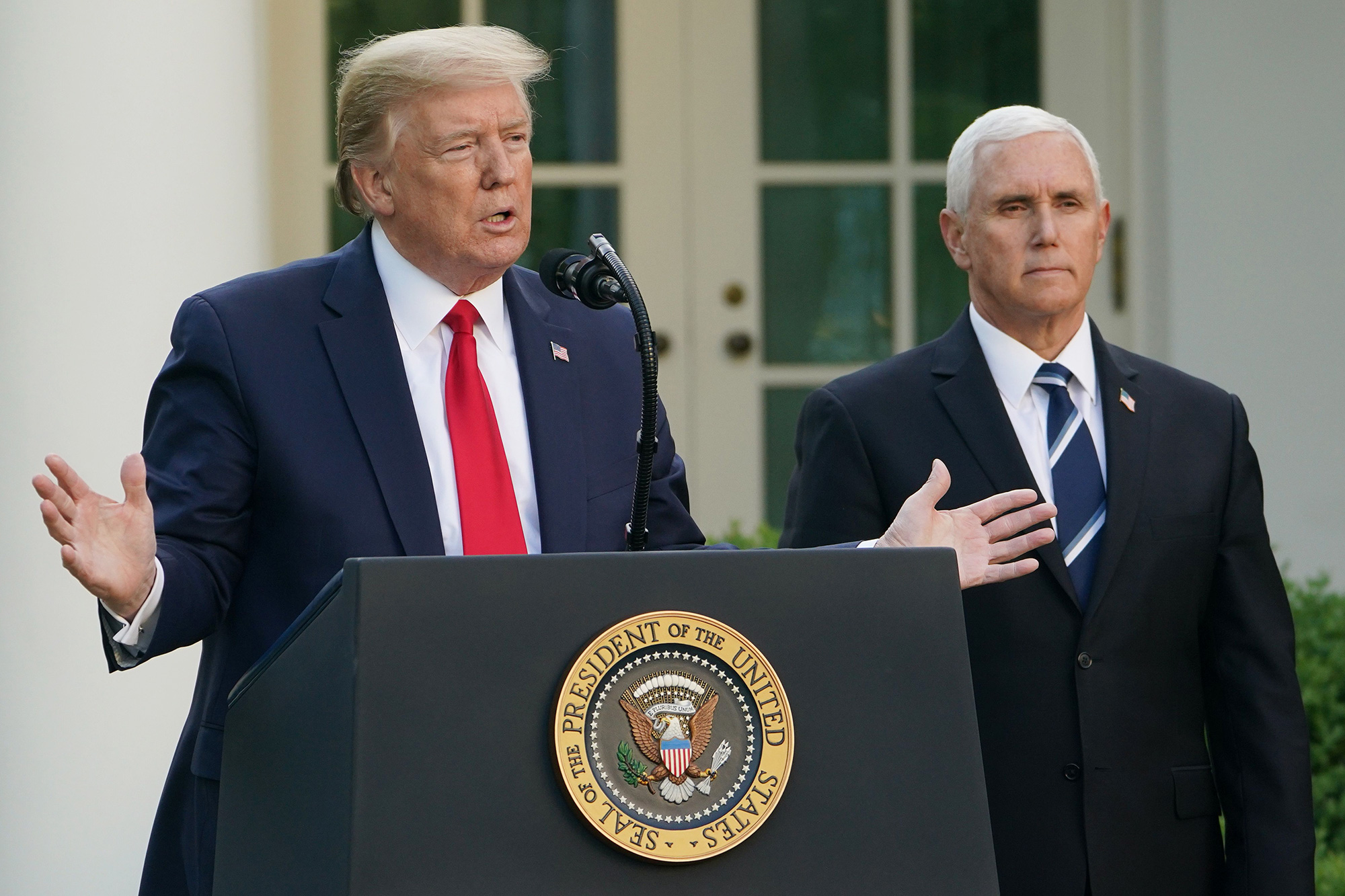 US President Donald Trump speaks as US Vice President Mike Pence looks on