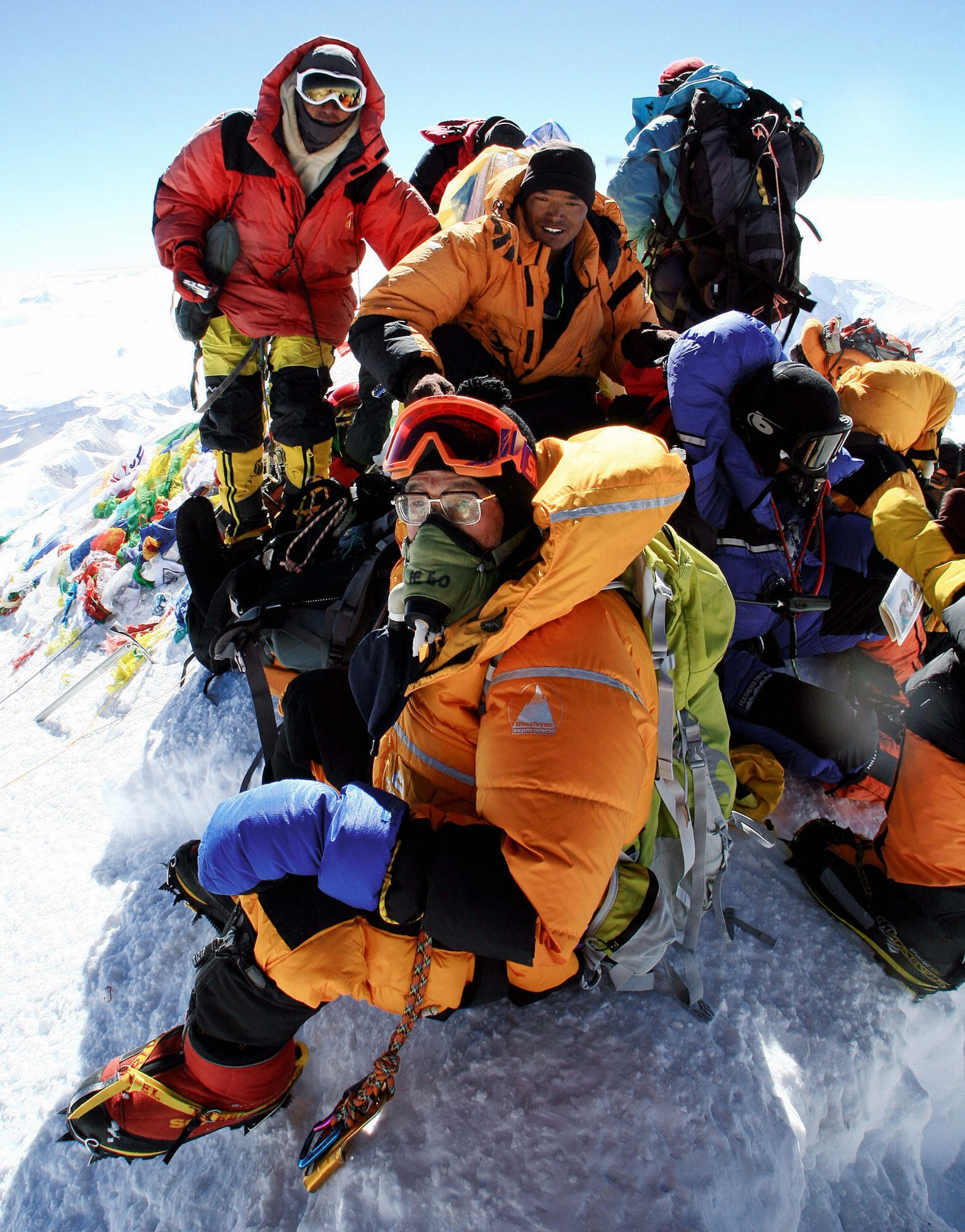 MOUNT EVEREST, NEPAL: In this picture taken, 22 May 2007, retired teacher and veteran mountaineer Katsusuke Yanagisawa, 71,(Foreground-C) rests along with others from his party on the summit of Mount Everest. As stated in a report released, 29 May 2007, a retired Japanese teacher aged 71 has become the world's oldest person to climb to the top of Mount Everest, according to a mountaineering group. The Japan Mountaineering Association said Katsusuke Yanagisawa reached the top of the world's highest mountain on May 22. AFP PHOTO/HAND OUT /HIRO (Photo credit should read HIRO YAMAGATA/AFP via Getty Images)