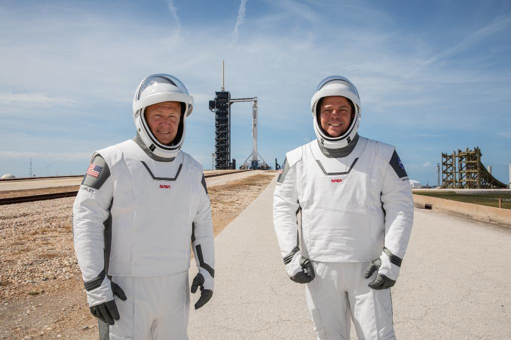 NASA astronauts Douglas Hurley, left, and Robert Behnken, wearing SpaceX spacesuits, stand in front of Launch Complex 39A