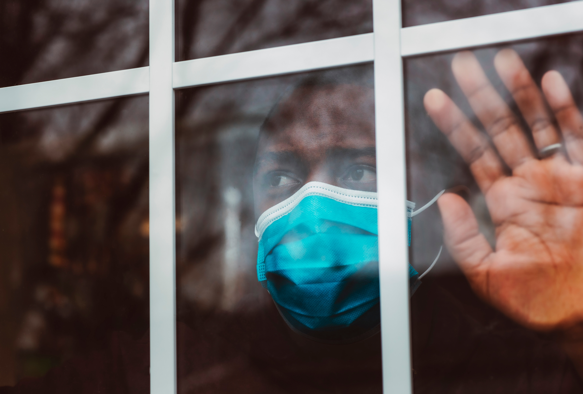 man looking out window wearing surgical mask