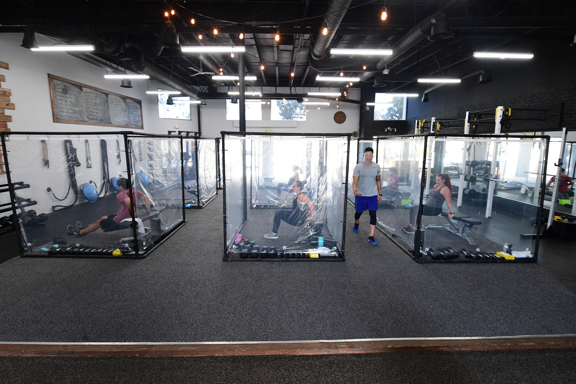 students behind plastic sheets in their workout pods