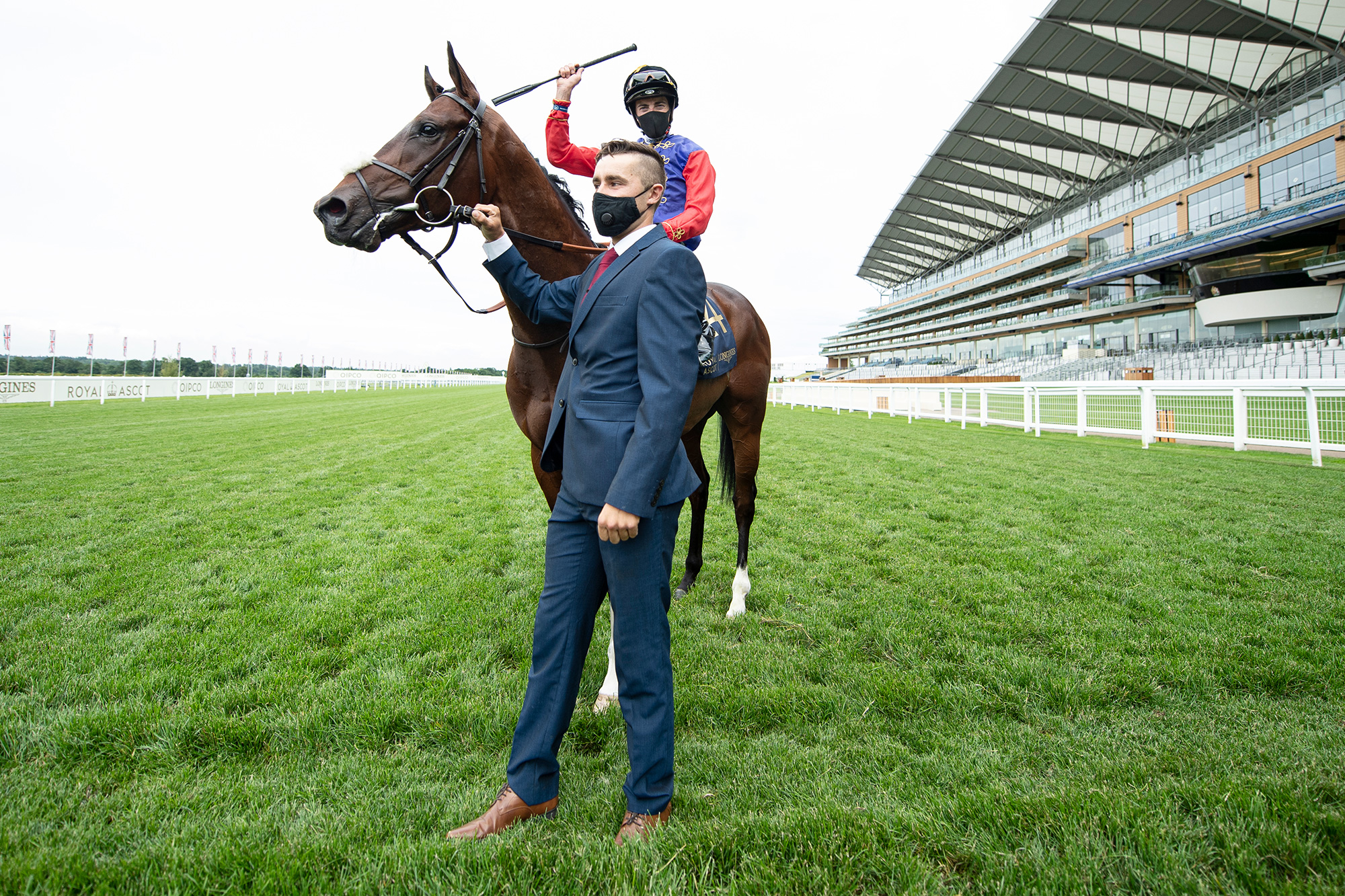 Jockey James Doyle celebrates after his victory on The Queens horse Tactical in The Windsor Castle Stakes and is held by his groom Nathan Cheshire during Day 2 of Royal Ascot